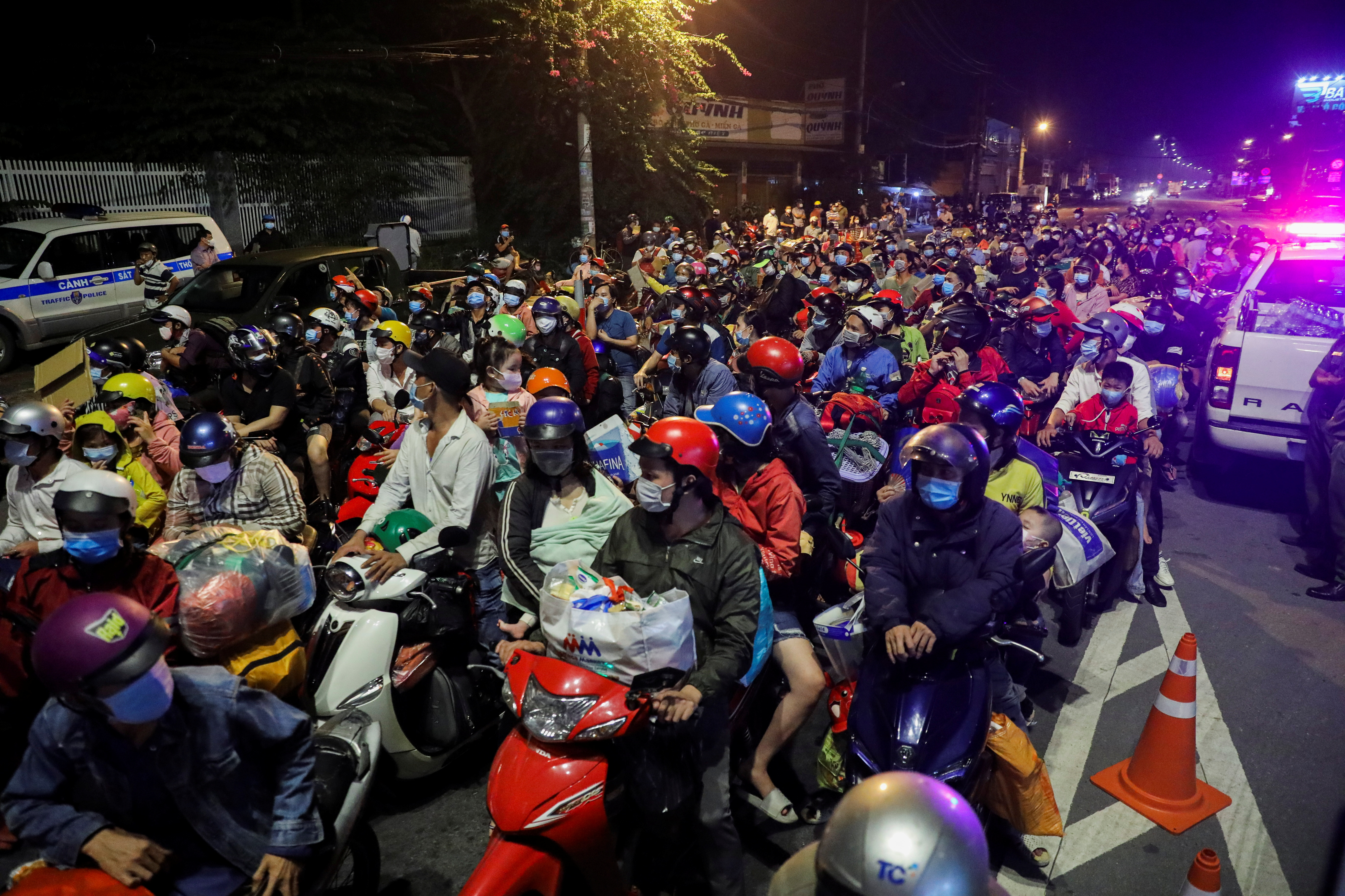 People, mostly migrant workers who are planning to return to their hometowns, wait at a checkpoint to leave Ho Chi Minh City, Vietnam September 30, 2021.   REUTERS/Stringer