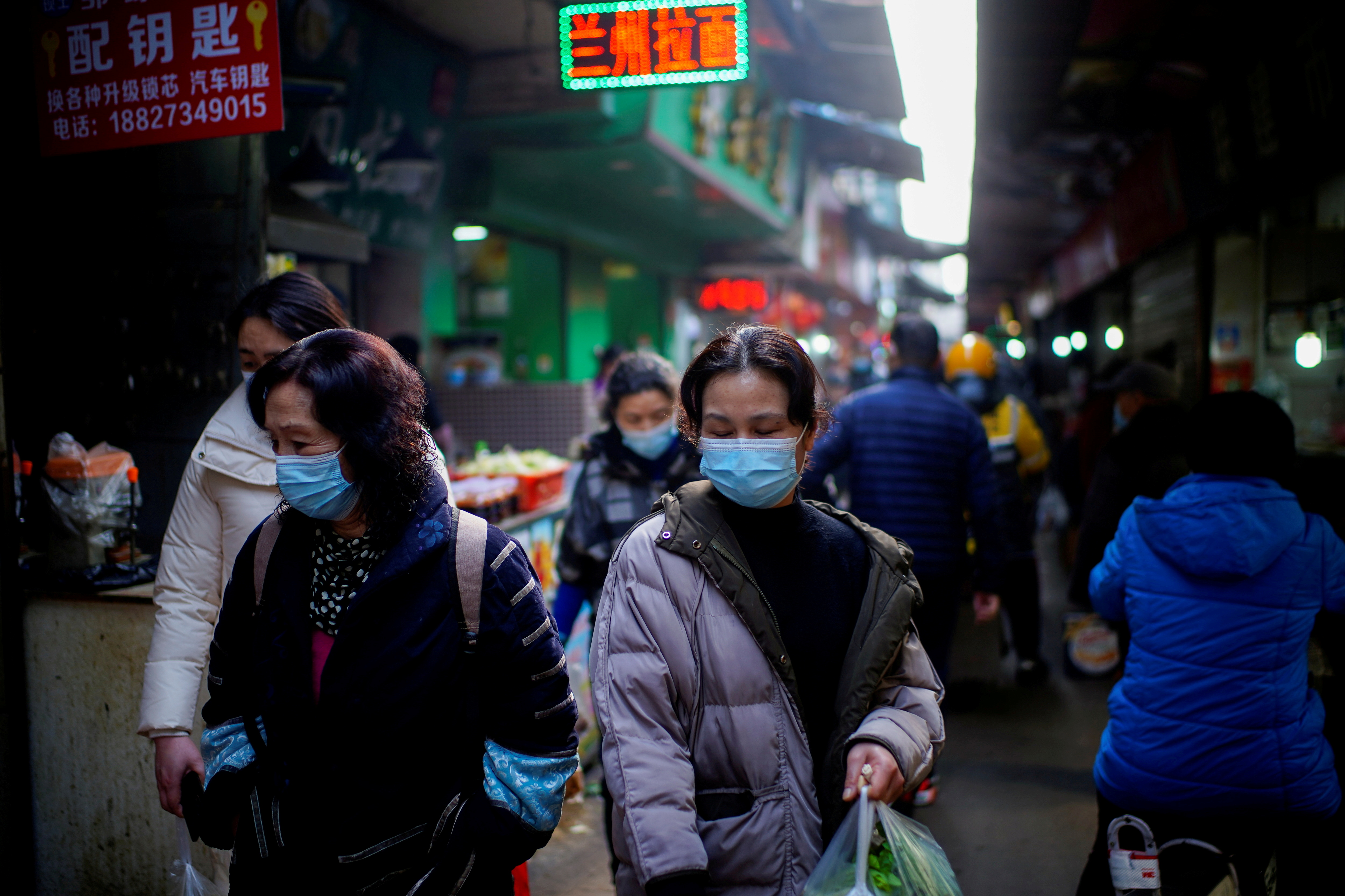 Pessoas usando máscaras caminham em um mercado de rua nos primeiros meses do surto da doença coronavírus (COVID-19) em Wuhan, província de Hubei, China, 8 de fevereiro de 2021. REUTERS / Aly Song / Foto de arquivo