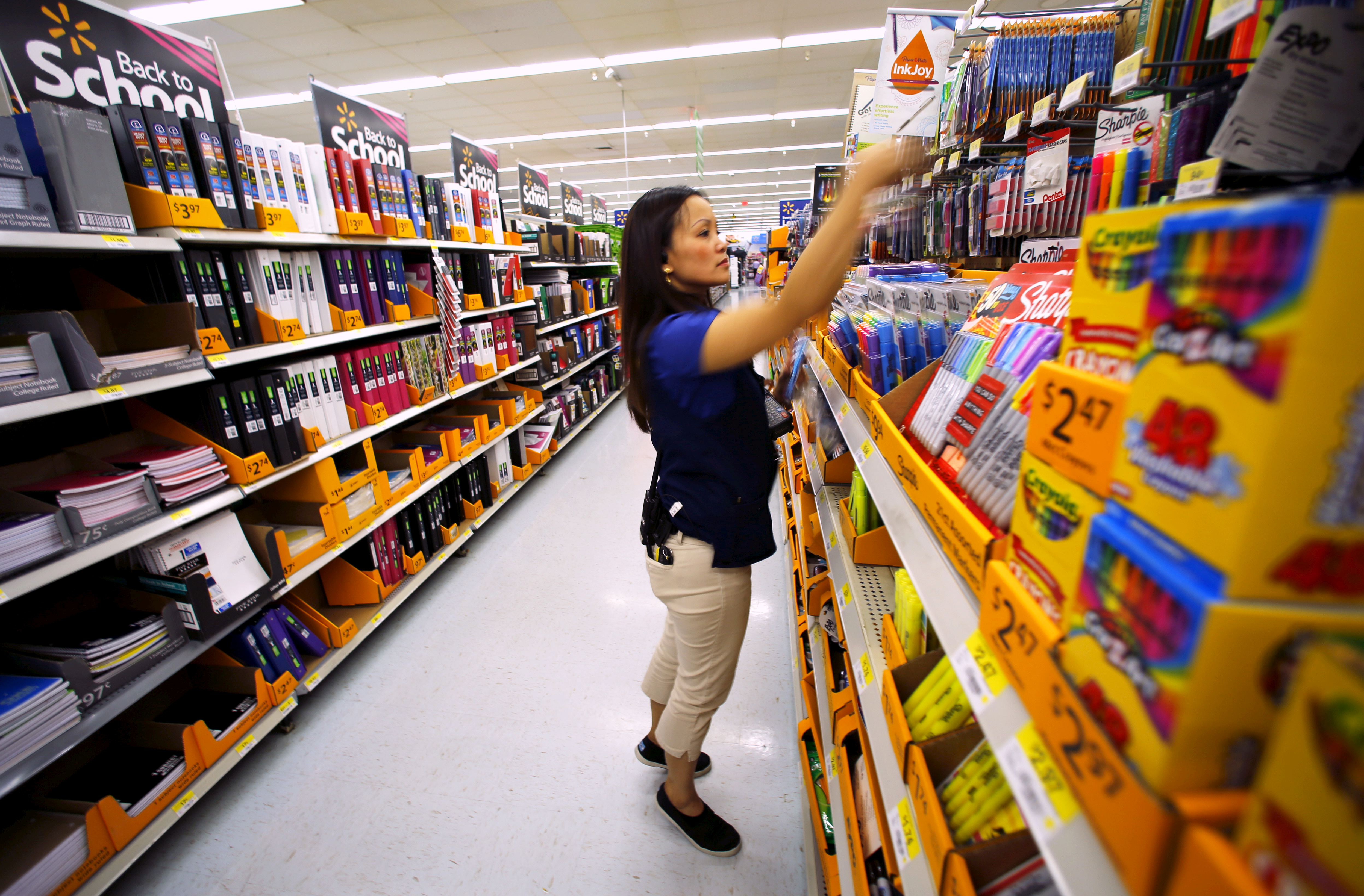 Walmart department manager Karren Gomes helps stock shelves with school supplies as the retail store prepare for back to school shoppers in San Diego, California, U.S. August 6, 2015. REUTERS/Mike Blake/File Photo