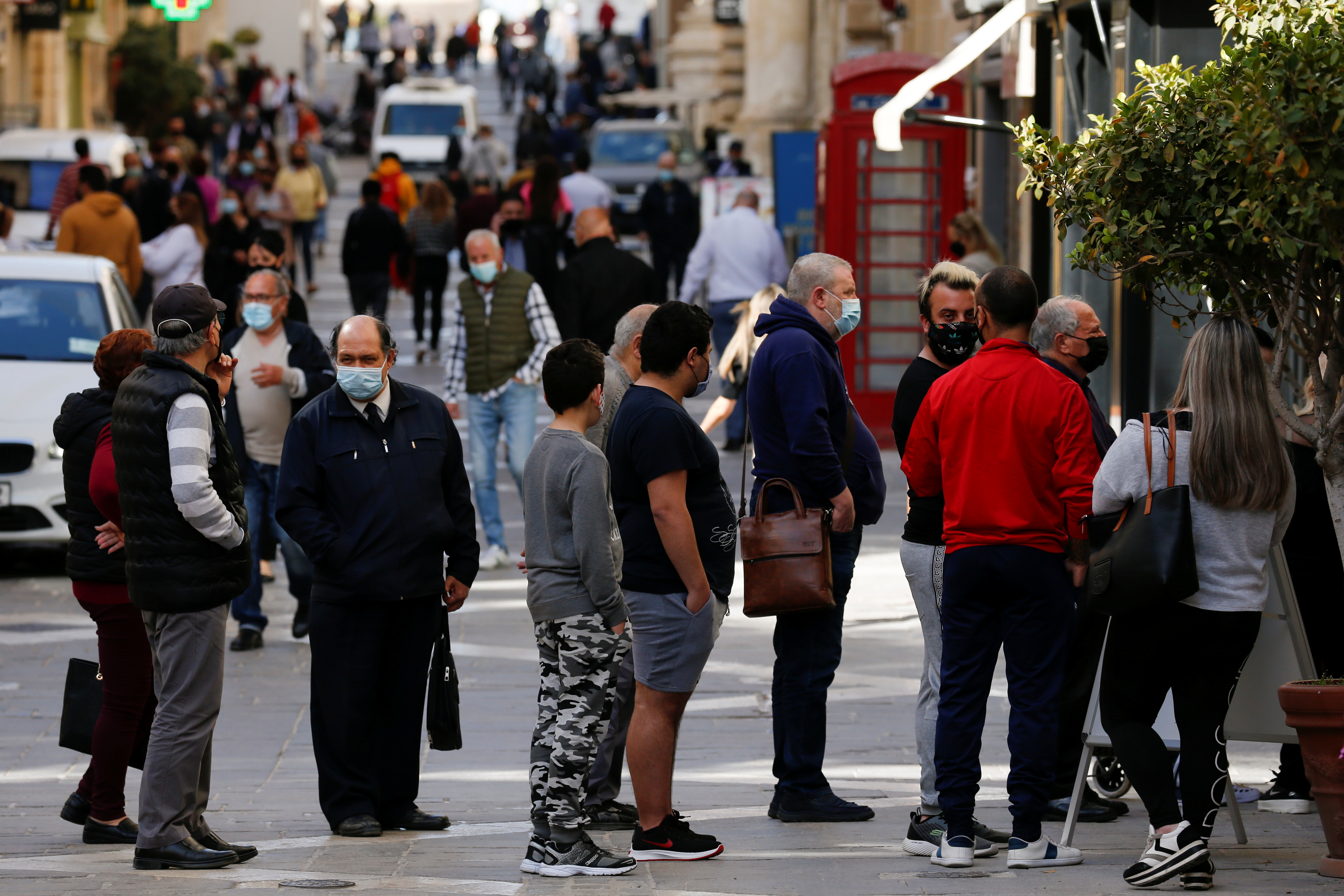 People wearing protective face masks queue to enter a shopping arcade as non-essential shops and services reopen for business after a seven-week-long shutdown because of the coronavirus disease (COVID-19) pandemic, in Valletta, Malta April 26, 2021. REUTERS/Darrin Zammit Lupi