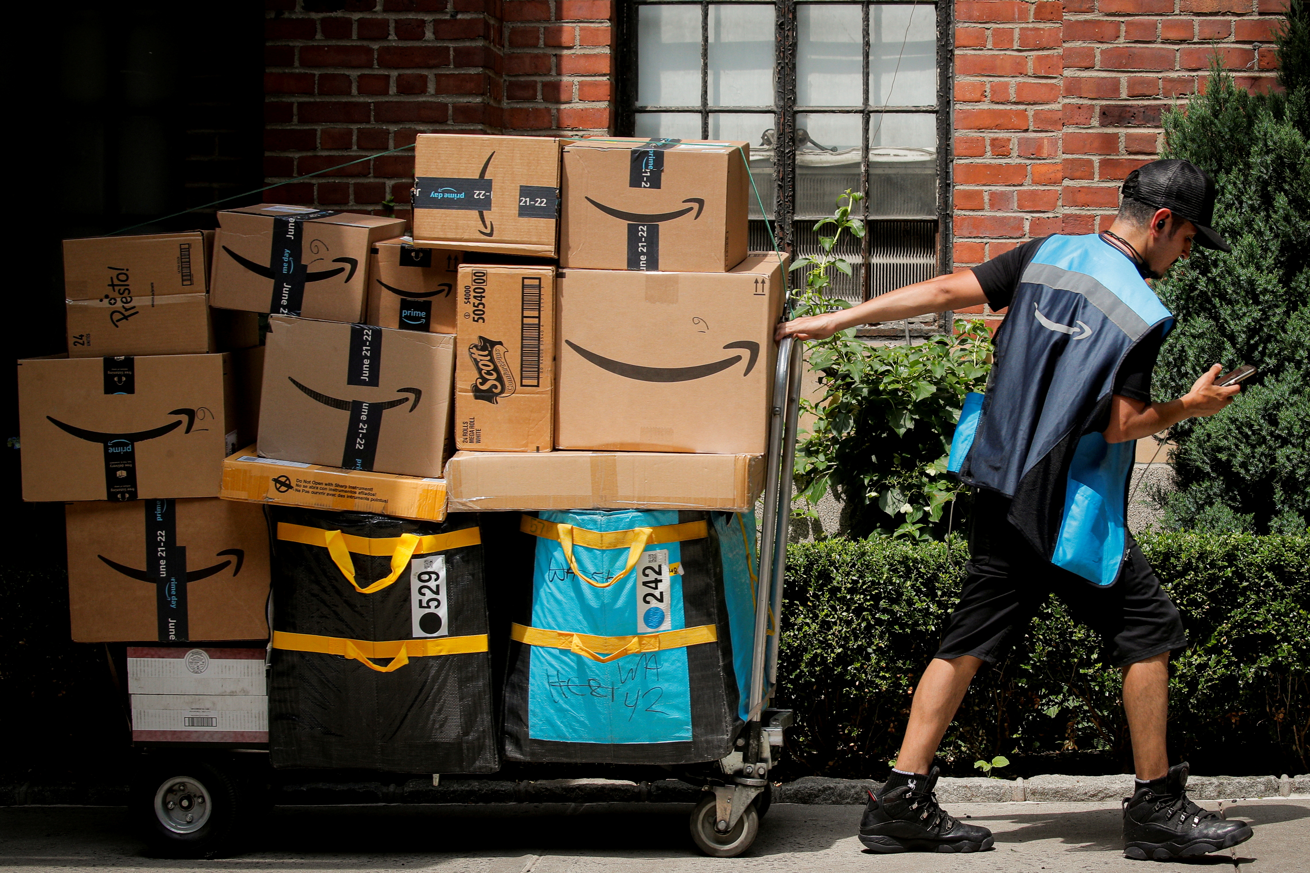 An Amazon delivery worker pulls a delivery cart full of packages during its annual Prime Day promotion in New York City, U.S., June 21, 2021.  REUTERS/Brendan McDermid/File Photo