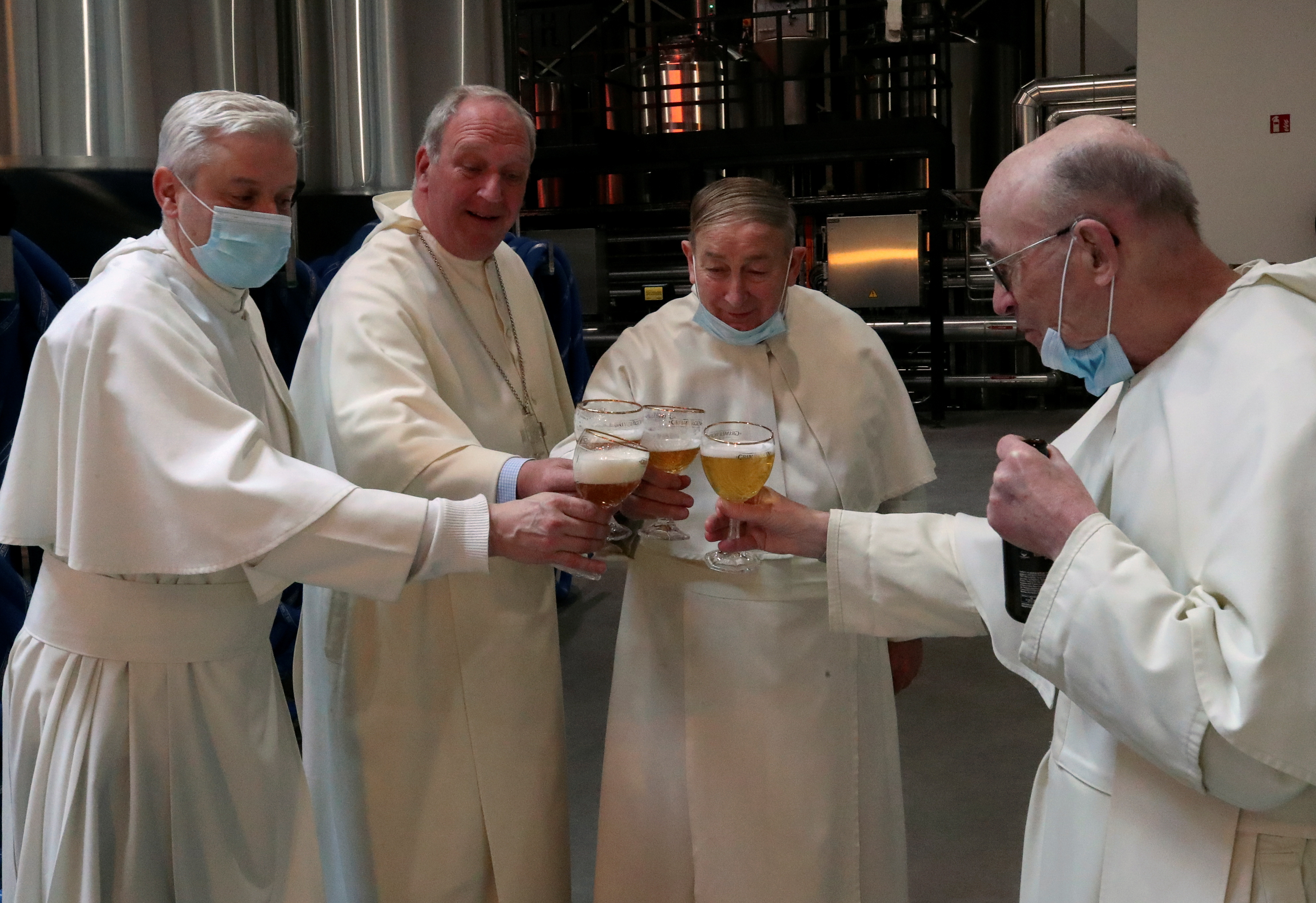 Prior Johan Goossens, abbot Erik De Sutter, father Stefaan Verstraeten and father Ton Smith toast after blessing beer tanks at the Belgian Abbey of Grimbergen, which returns to brewing after a break of more than 200 years with a new microbrewery in Grimbergen, Belgium May 26, 2021. REUTERS/Yves Herman