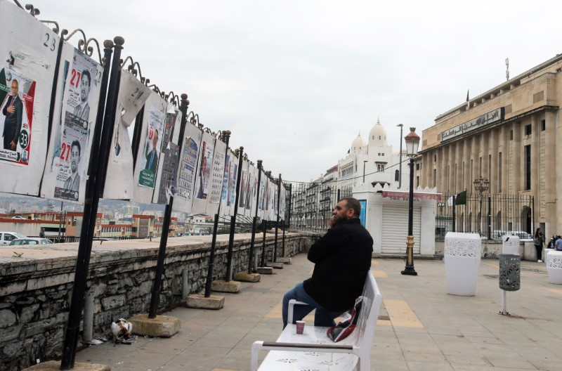 A man sits in front of parliamentary election campaign posters, ahead of the legislative elections, near the National People's Assembly in Algiers, Algeria June 6, 2021. REUTERS/Ramzi Boudina
