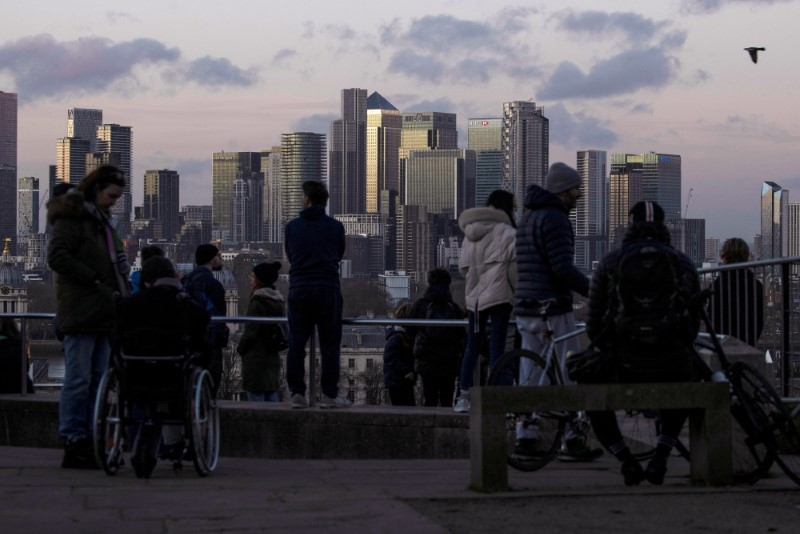 People look towards Canary Wharf from Greenwich Park in London, Britain December 27, 2020. REUTERS/Simon Dawson