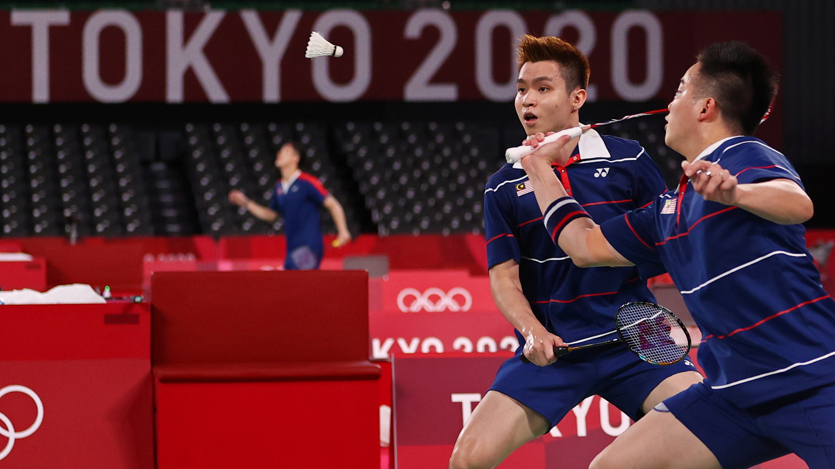 Tokyo 2020 Olympics - Badminton - Men's Doubles - Quarterfinal - MFS - Musashino Forest Sport Plaza, Tokyo, Japan – July 29, 2021. Aaron Chia of Malaysia in action as Soh Wooi Yik of Malaysia looks on during the match against Marcus Fernaldi Gideon of Indonesia and Kevin Sanjaya Sukamuljo of Indonesia. REUTERS/Hamad I Mohammed