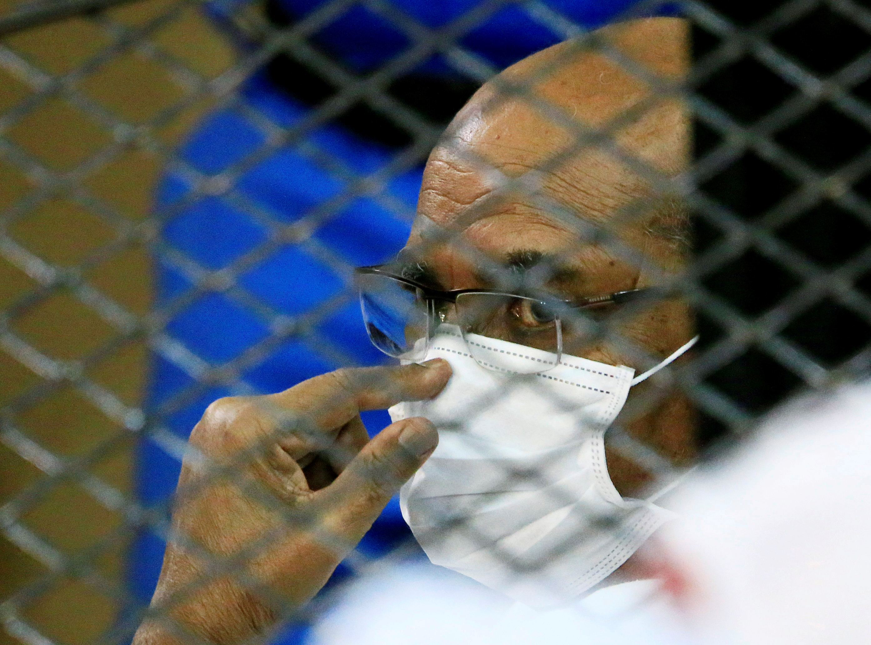 Sudan's ousted President Omar al-Bashir is seen inside the defendant's cage during his and some of his former allies trial over the 1989 military coup that brought the autocrat to power in 1989, at a courthouse in Khartoum, Sudan September 15, 2020. REUTERS/Mohamed Nureldin Abdallah/File Photo