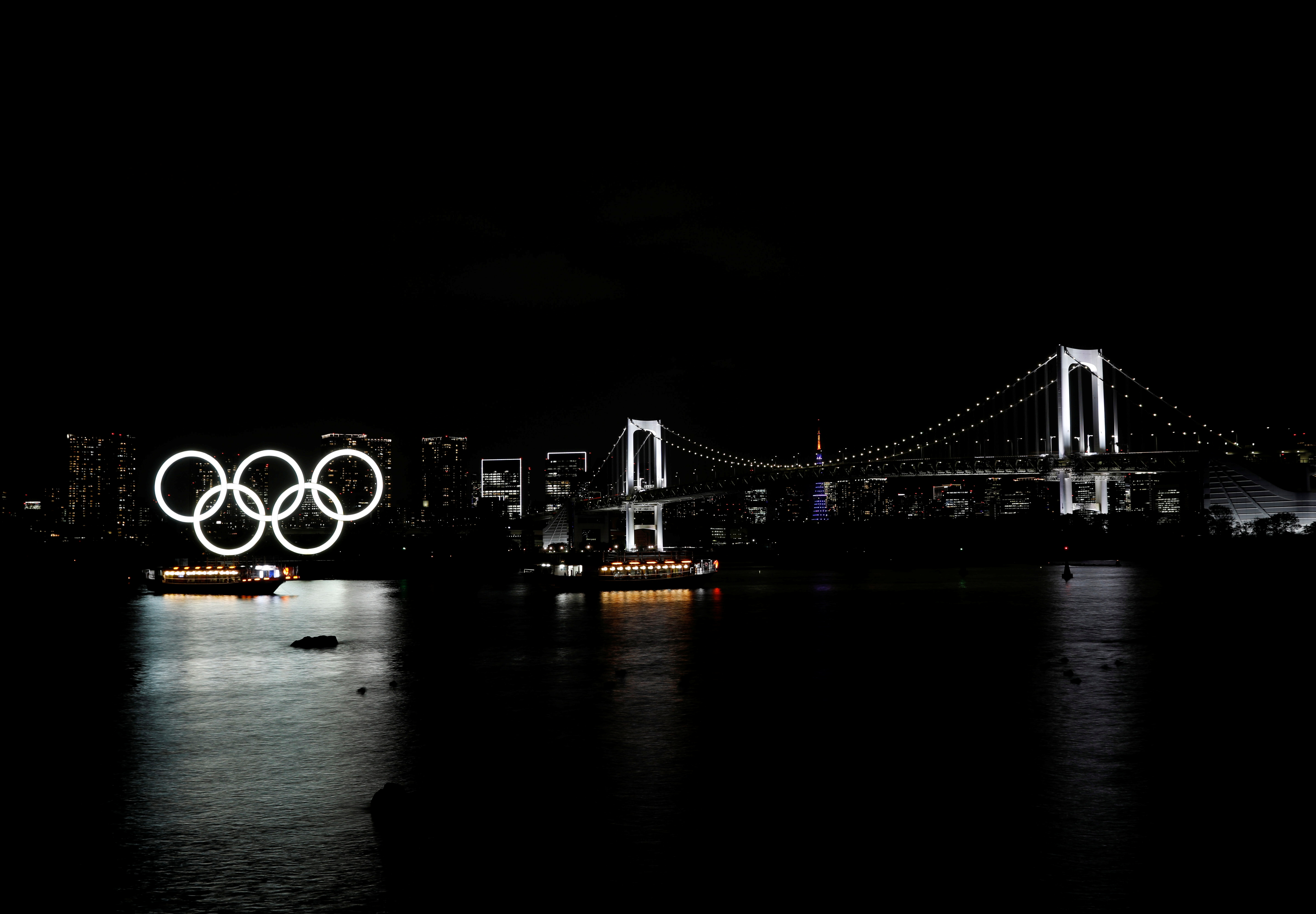 Boats sail past the giant Olympic rings and the Rainbow Bridge on the waterfront area of Odaiba Marine Park in Tokyo, Japan, April 2, 2021. REUTERS/Kim Kyung-Hoon