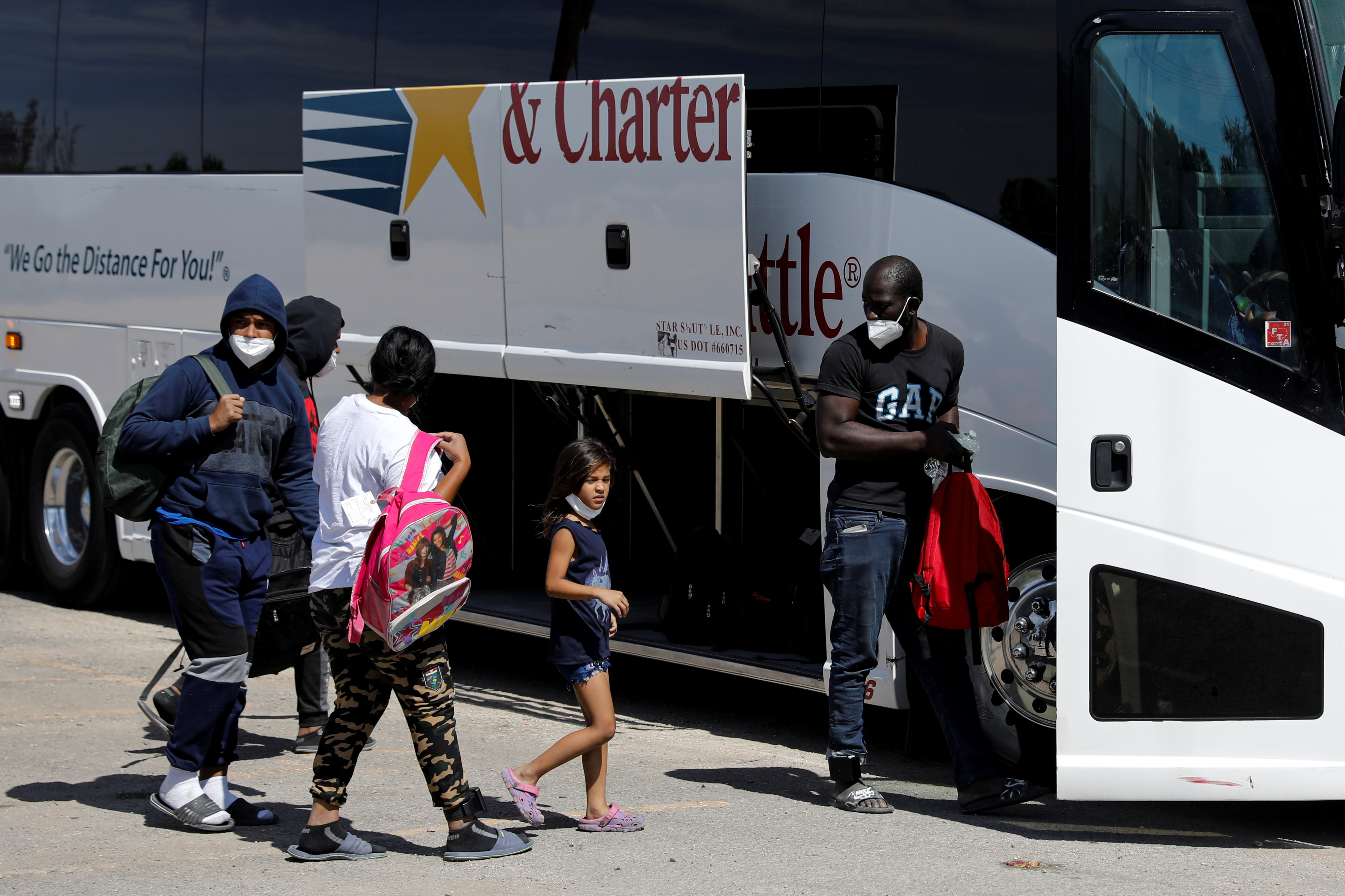 Migrants seeking asylum in the U.S. board a bus to Houston from Val Verde Border Humanitarian Coalition after being released from U.S. Customs and Border Protection, in Del Rio, Texas, U.S., September 22, 2021. REUTERS/Marco Bello