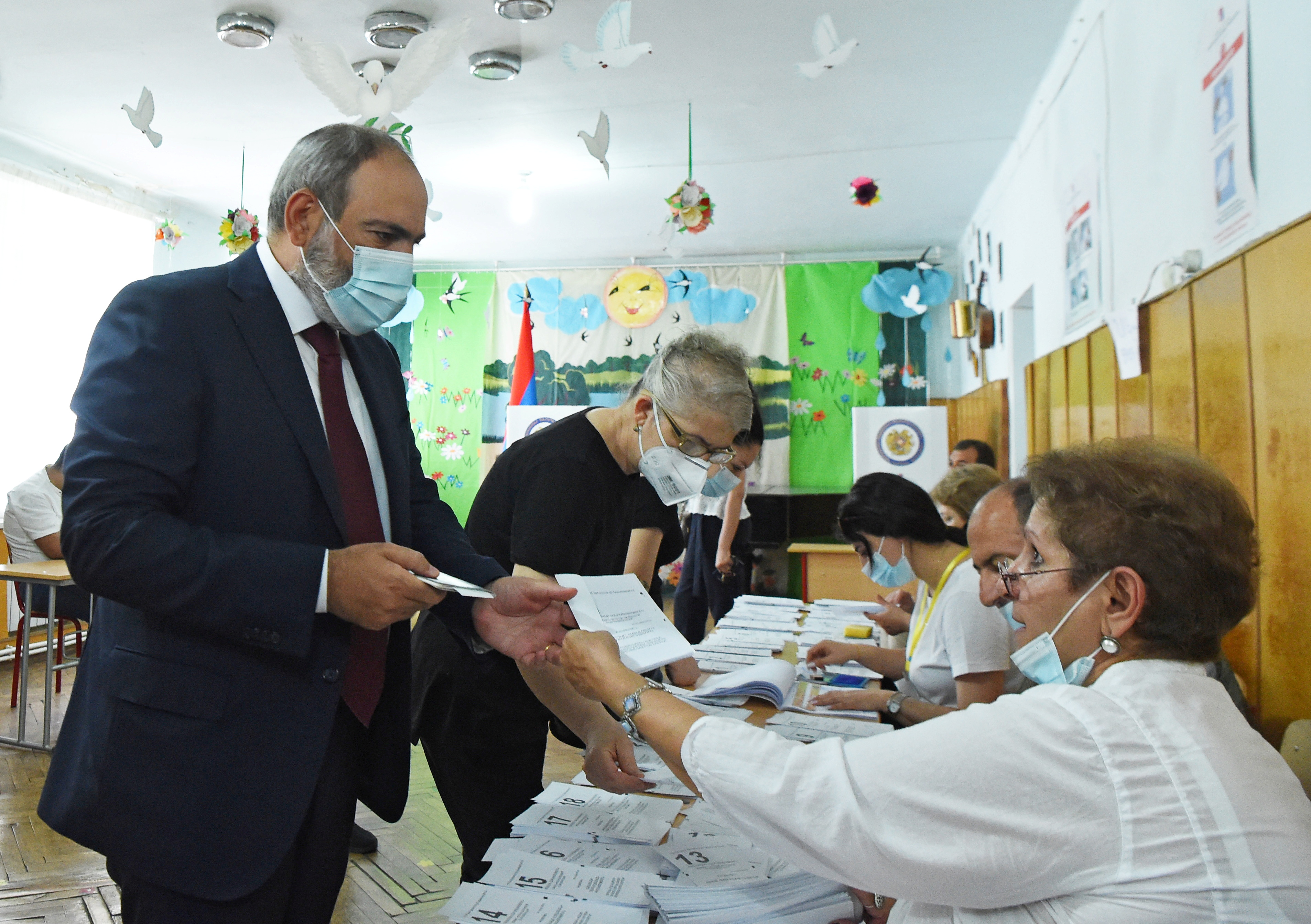 Armenia's acting Prime Minister and leader of Civil Contract party Nikol Pashinyan receives a ballot at a polling station during the snap parliamentary election in Yerevan, Armenia June 20, 2021. Lusi Sargsyan/Photolure via REUTERS