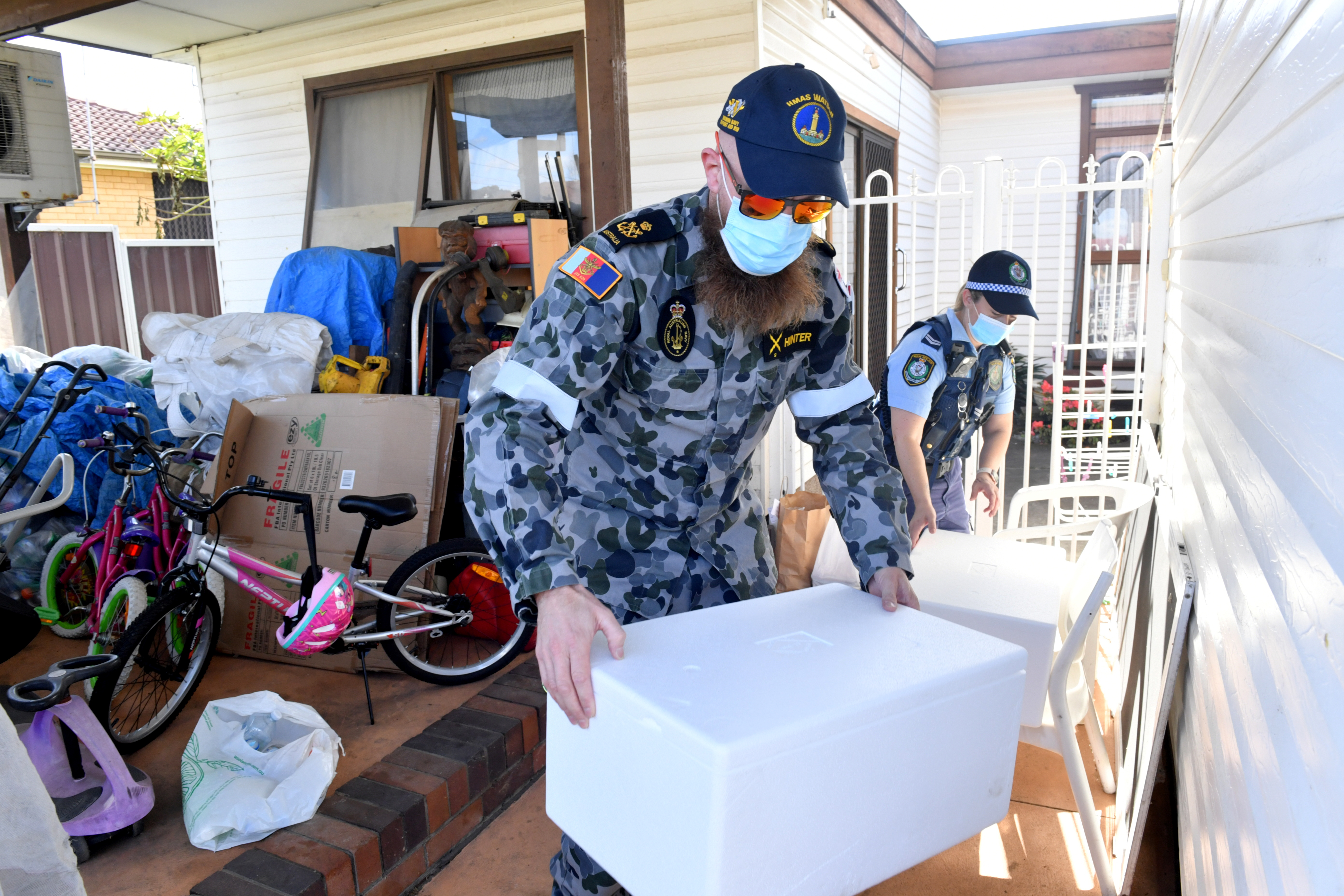 Australian Defence Force personnel and NSW police deliver emergency food parcels for people in lockdown in the Fairfield suburb in the southwest of Sydney, Australia, August 2, 2021.  AAP Image/Mick Tsikas via REUTERS