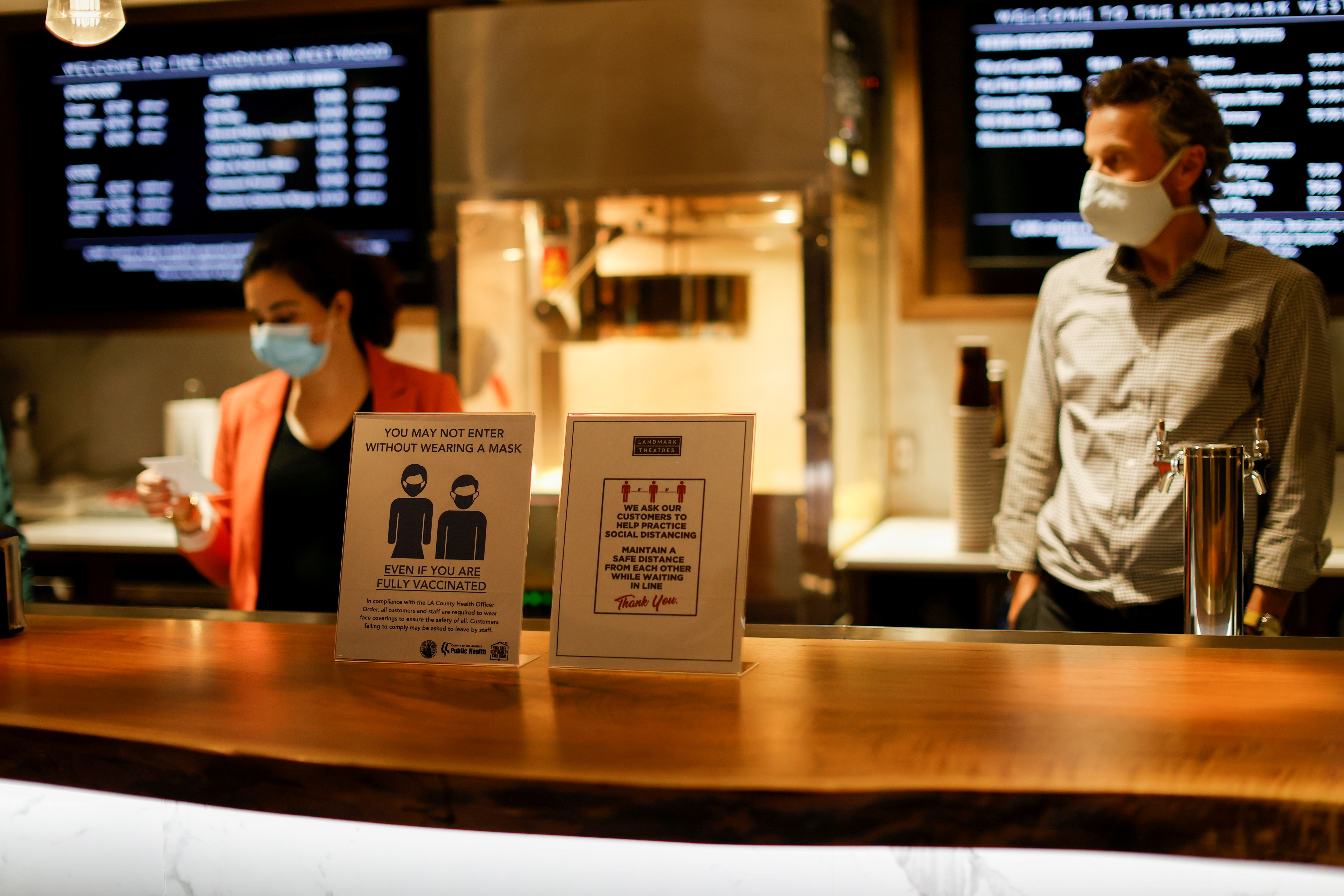 Signs advising about masks and social distancing are pictured by concessions at the Landmark Westwood theatre in Los Angeles, California, U.S., May 14, 2021.  REUTERS/Mario Anzuoni/File Photo