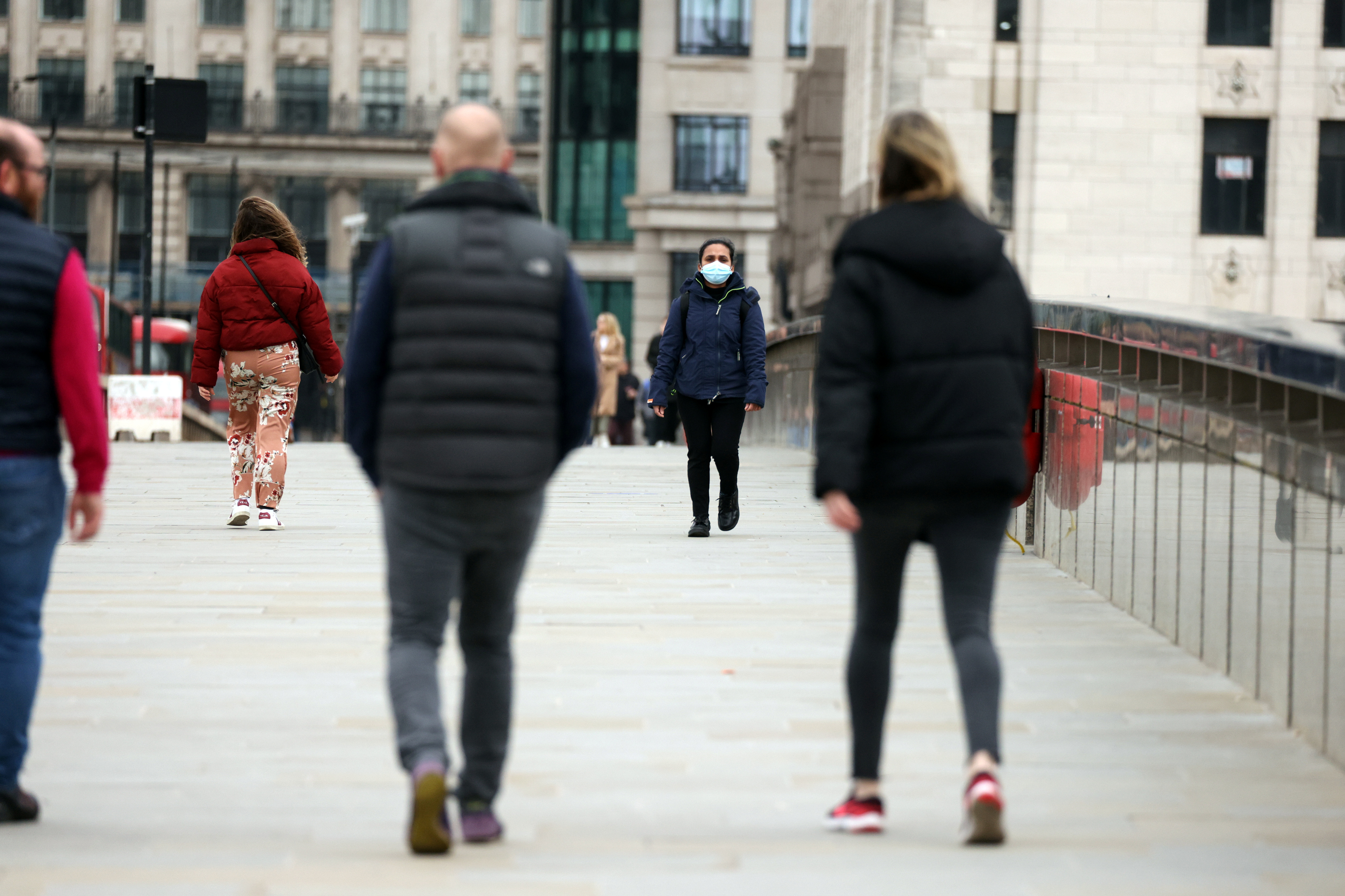 People socially distance while walking across London Bridge as coronavirus disease (COVID-19) lockdown restrictions begin to ease, allowing groups of 6 to meet up outside starting from Monday March 29, in London, Britain, March 28, 2021. REUTERS/Kevin Coombs