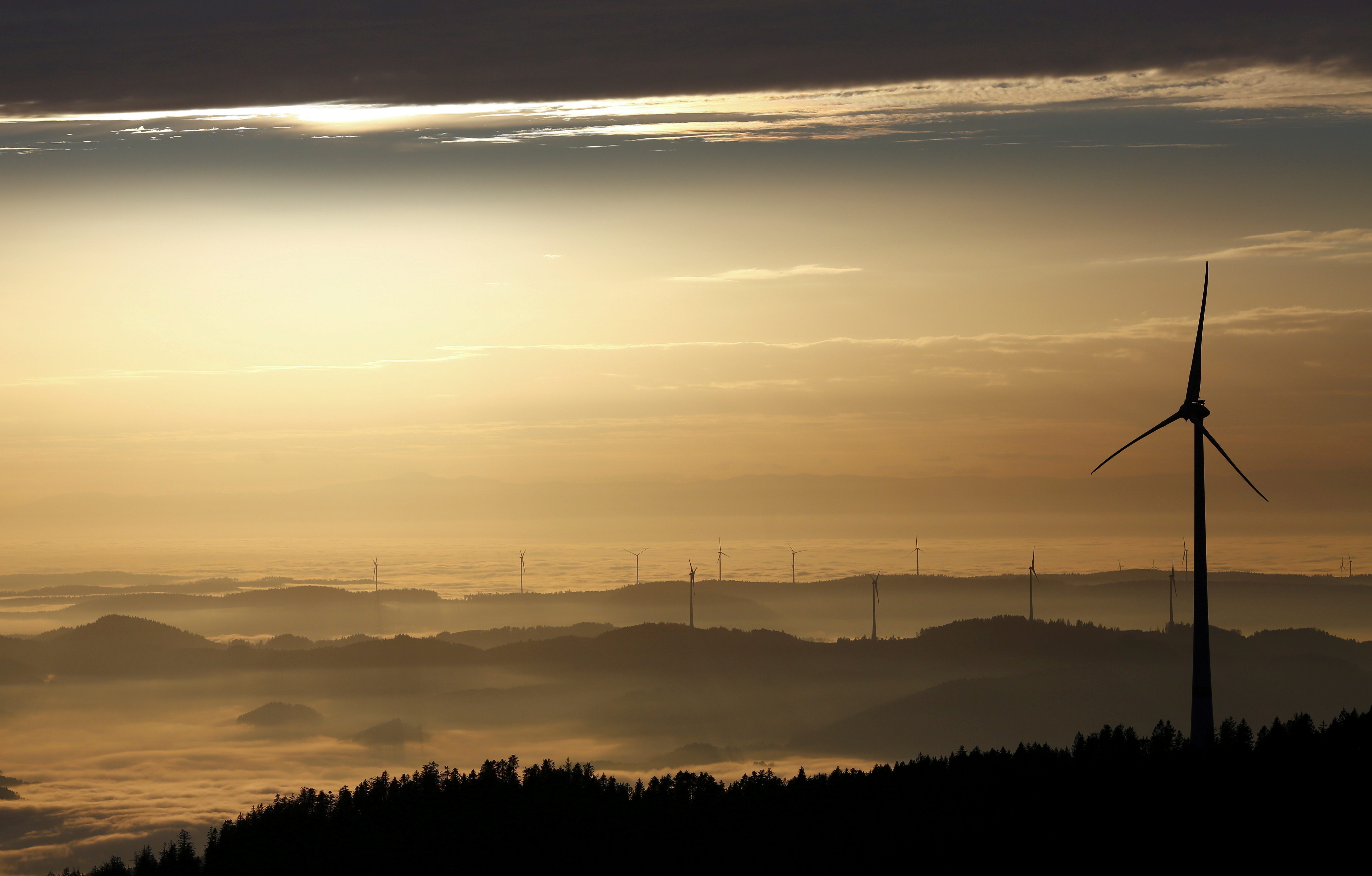 A wind turbine stands out against the sky as the sun sets over the Black Forest with the French mountain range of the Vosges in rear, November 10, 2020.   REUTERS/Joachim Herrmann/File Photo