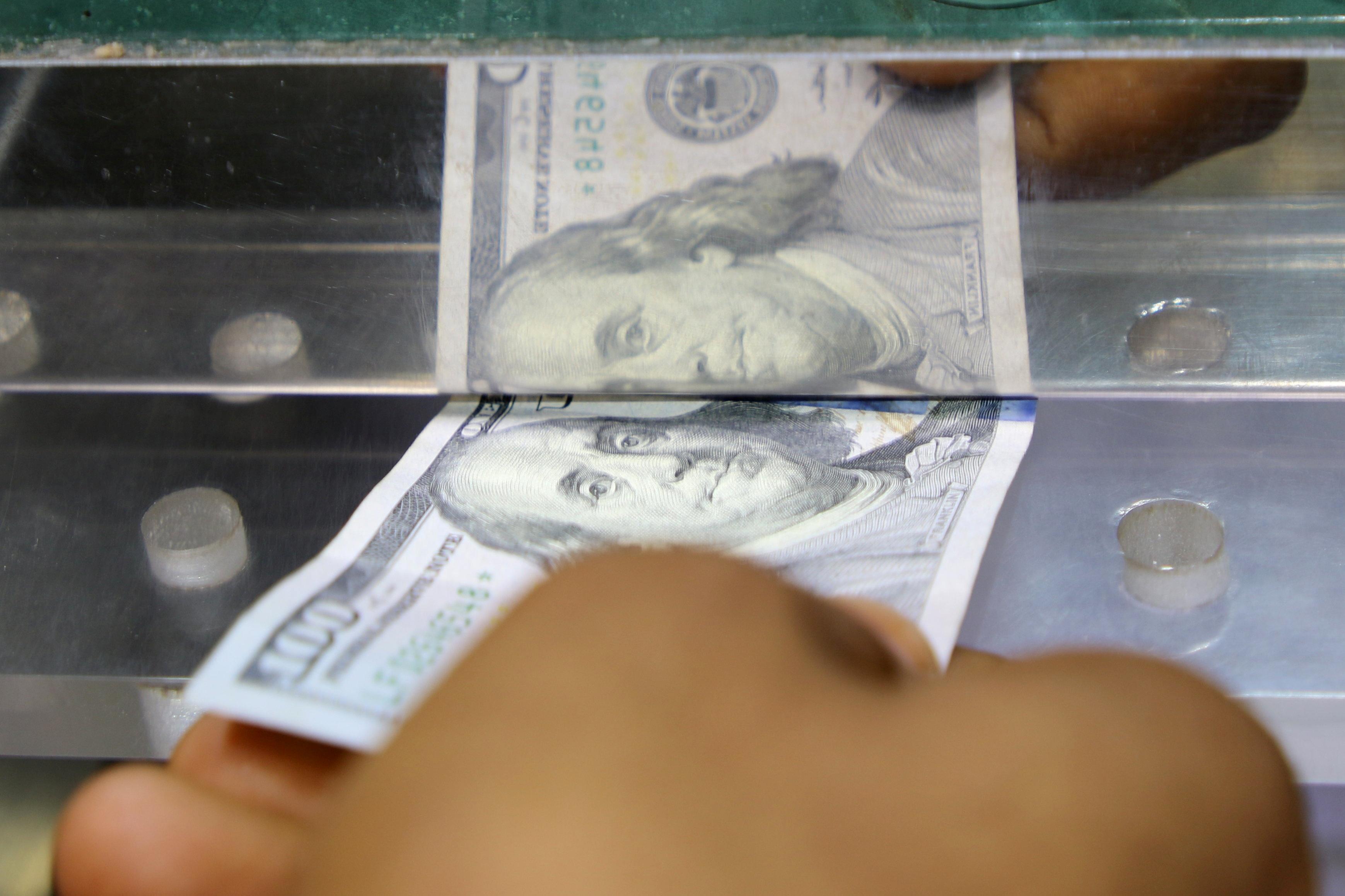 A man inserts a U.S. dollar banknote into the window of a local currency exchange in Aden, Yemen June 29, 2021.  REUTERS/Fawaz Salman