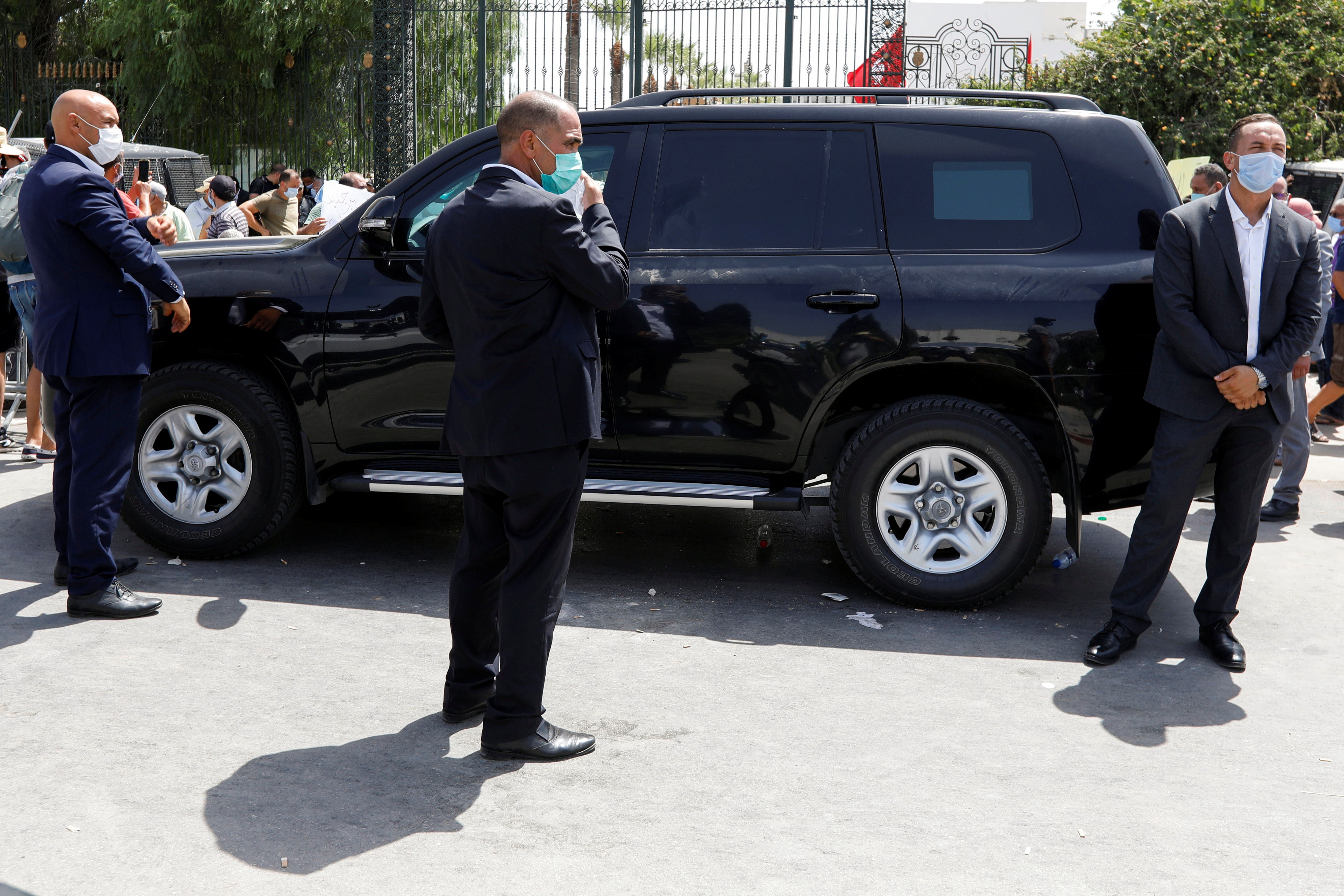 Security personnel keep guard around a vehicle carrying Parliament Speaker Rached Ghannouchi as his supporters gather outside the parliament building in Tunis, Tunisia July 26, 2021. REUTERS/Zoubeir Souissi