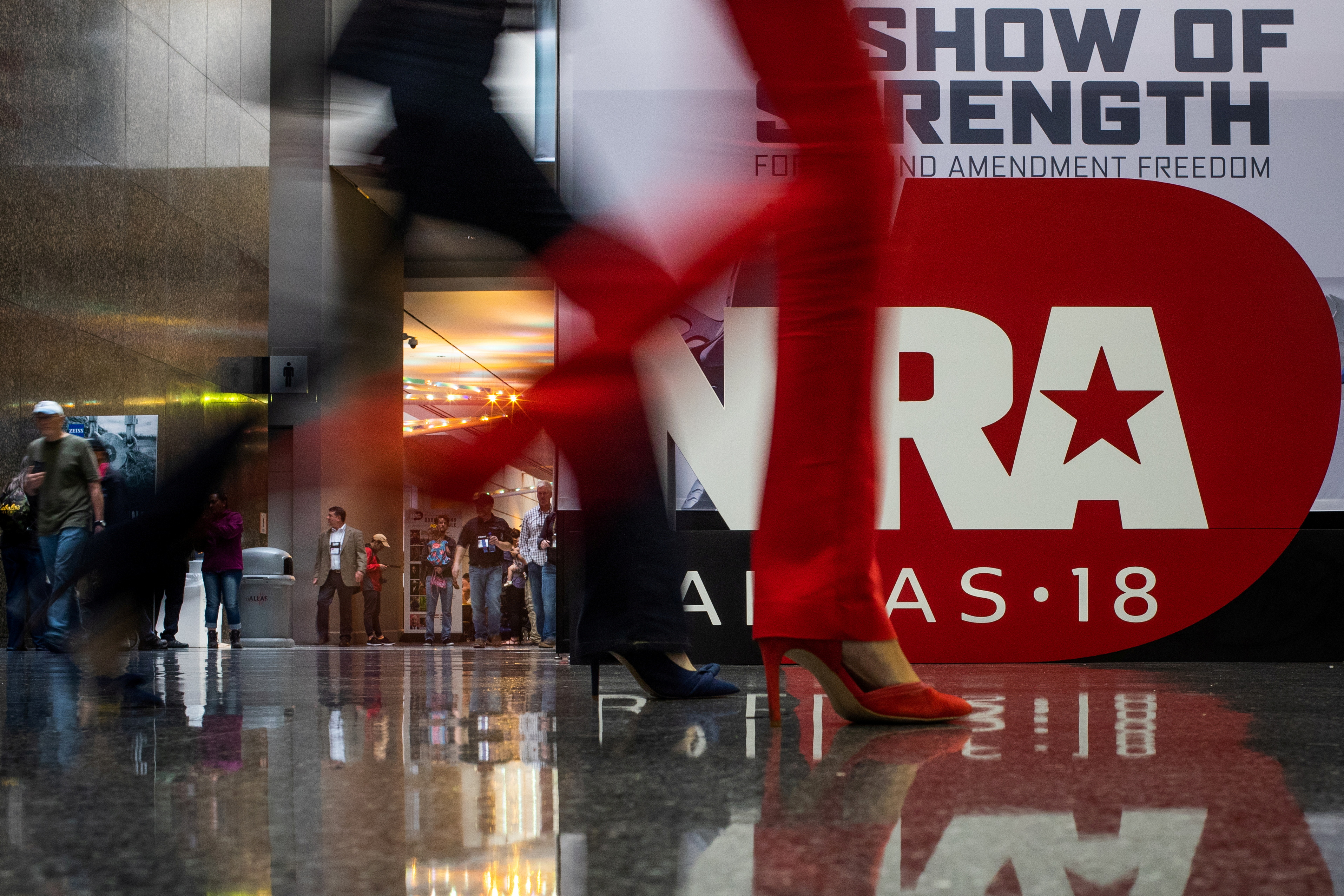 Attendees walk past a sign at the annual National Rifle Association (NRA) meeting in Dallas, Texas, U.S., May 4, 2018. REUTERS/Adrees Latif