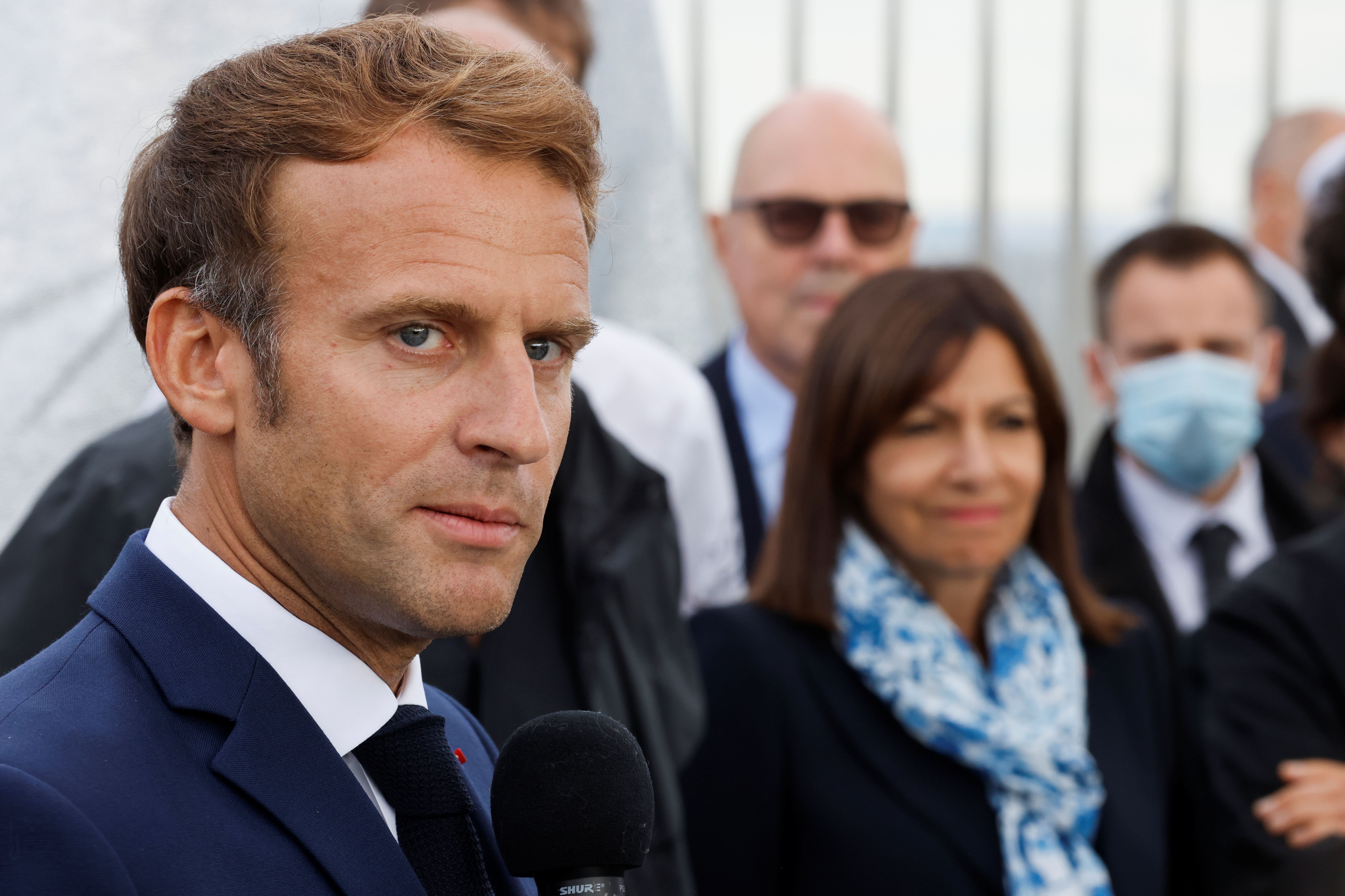 French President Emmanuel Macron speaks near Paris Mayor and Socialist Party (PS) candidate for the 2022 French presidential elections Anne Hidalgo during the inauguration of the wrapped Arc de Triomphe, designed by the late artist Christo, in Paris, France, September 16, 2021. Ludovic Marin/Pool via REUTERS