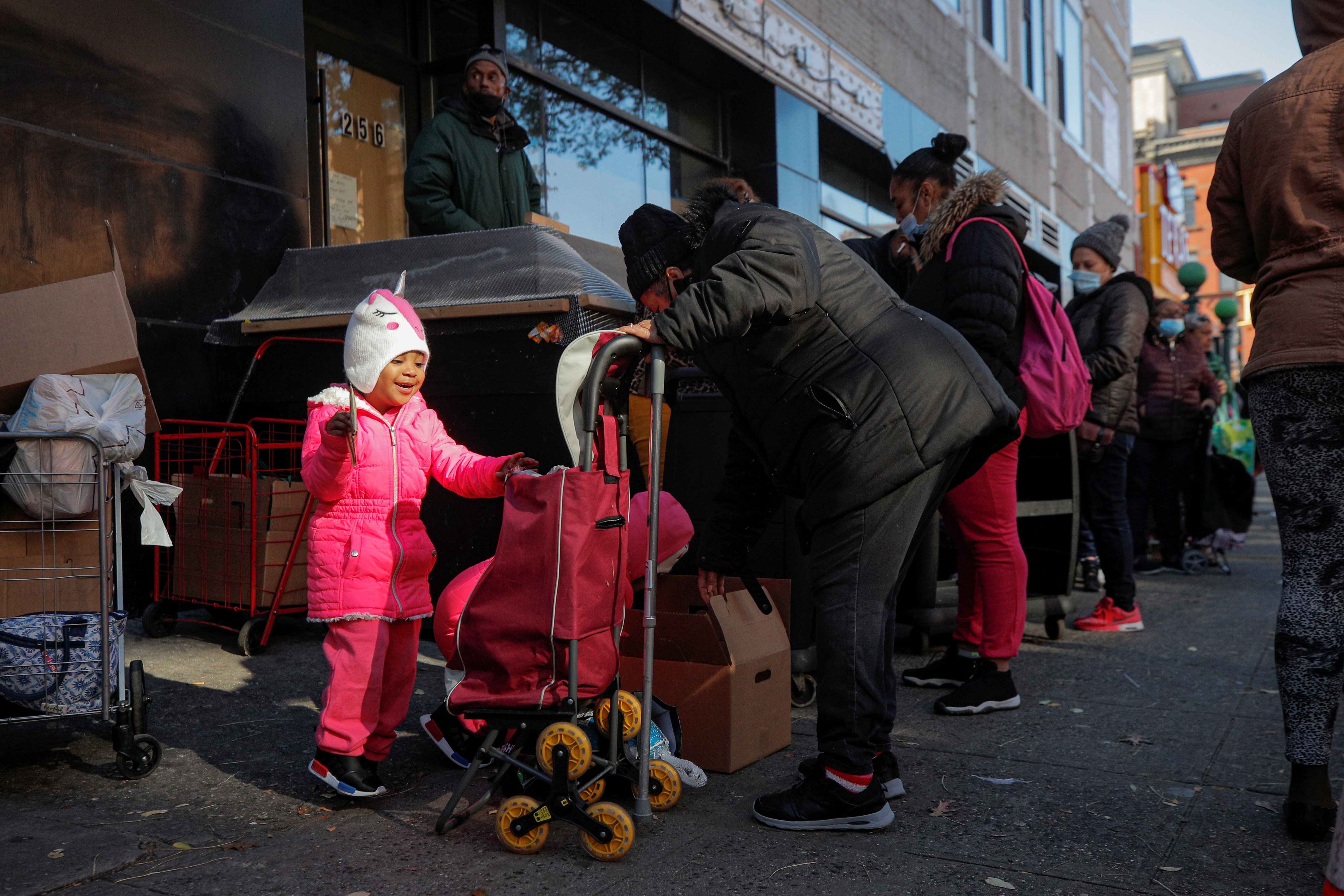 A child reacts as she helps to load a cart after receiving a holiday box of food from the Food Bank For New York City ahead of the Thanksgiving holiday, as the global outbreak of the coronavirus disease (COVID-19) continues, in the Harlem neighborhood of New York, U.S., November 16, 2020.  REUTERS/Brendan McDermid