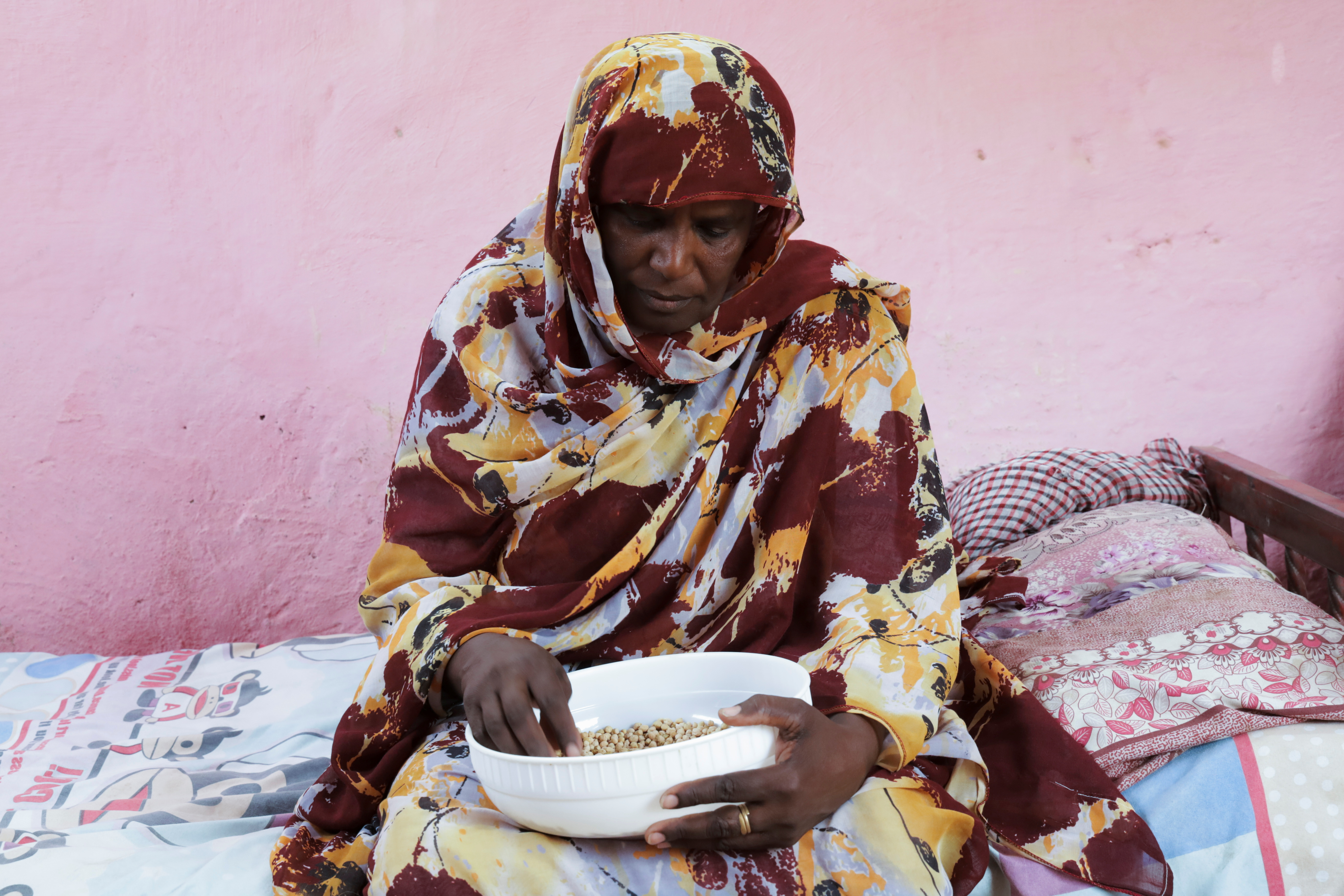 Magda Ahmed, Sudanese mother of orphan children who applied for Sudan's Thamarat Family Support Programme, holds a bowl of food in South Khartoum April 26, 2021. REUTERS/El-Tayeb Siddig