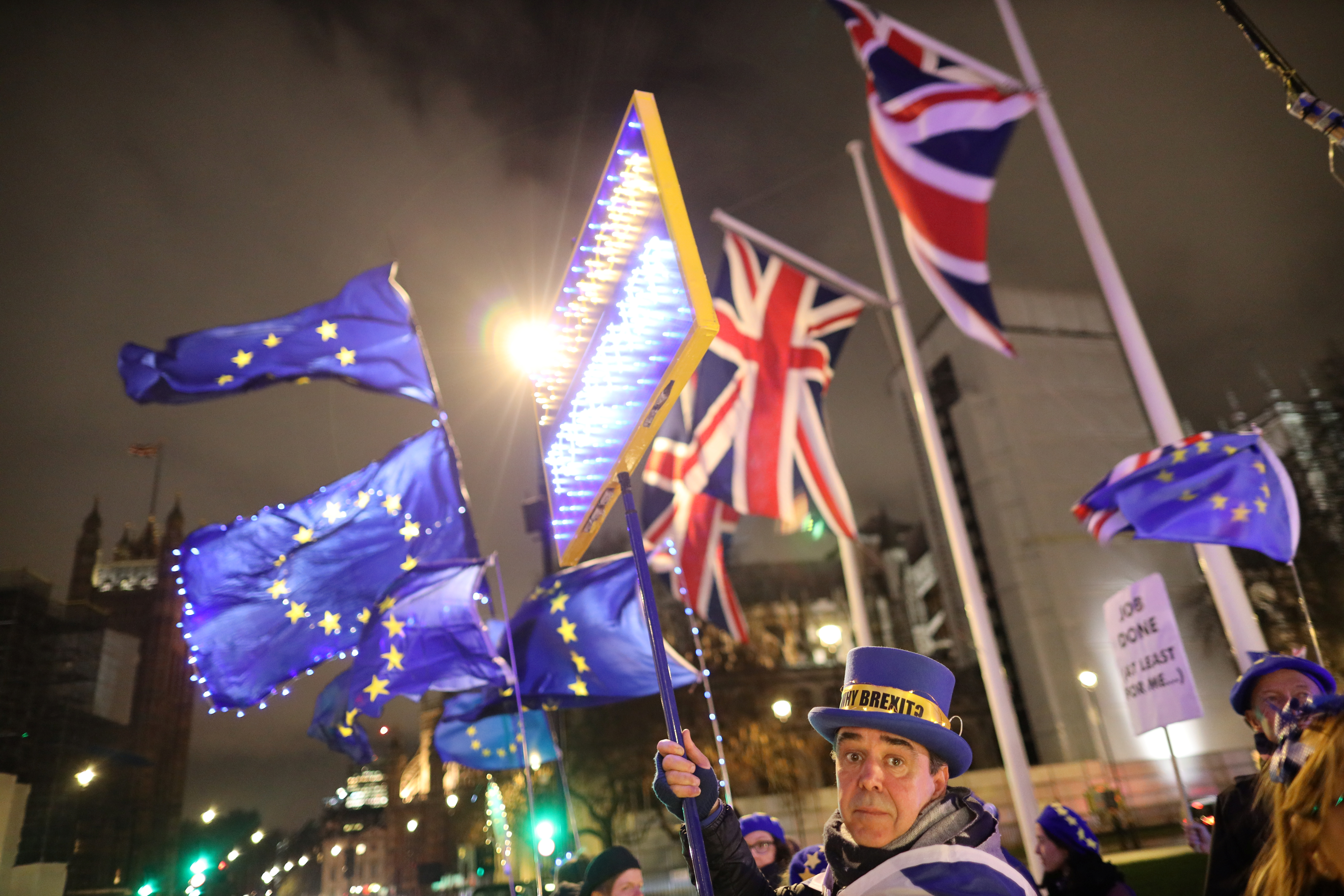 Anti-Brexit-demonstranter som håller en banner och flaggor demonstrerar utanför parlamentet i London, Storbritannien den 30 januari 2020. REUTERS / Antonio Bronic