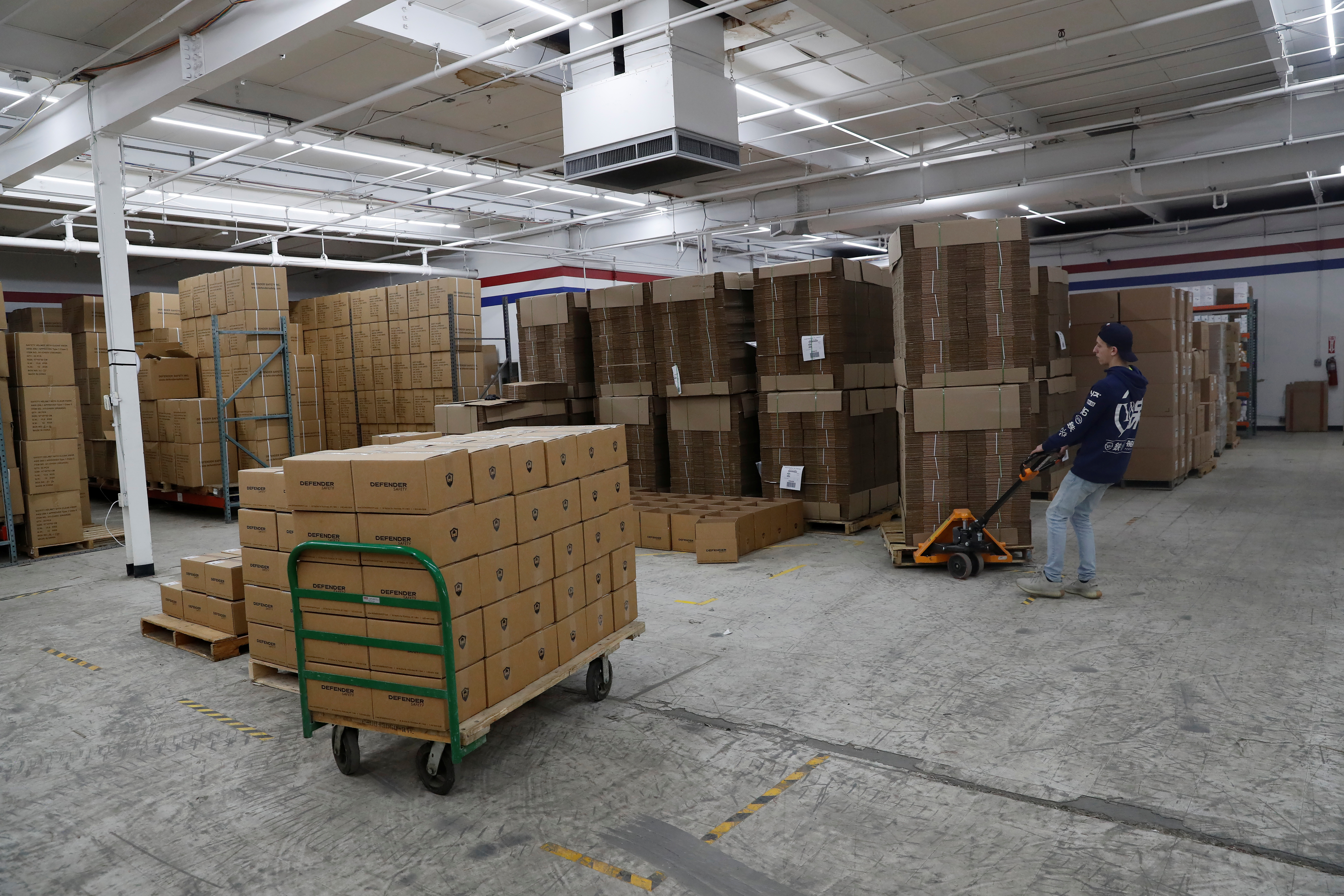 An employee of Defender Safety moves products inside their warehouse in Plainview, New York, U.S., March 24, 2021. REUTERS/Shannon Stapleton/File Photo