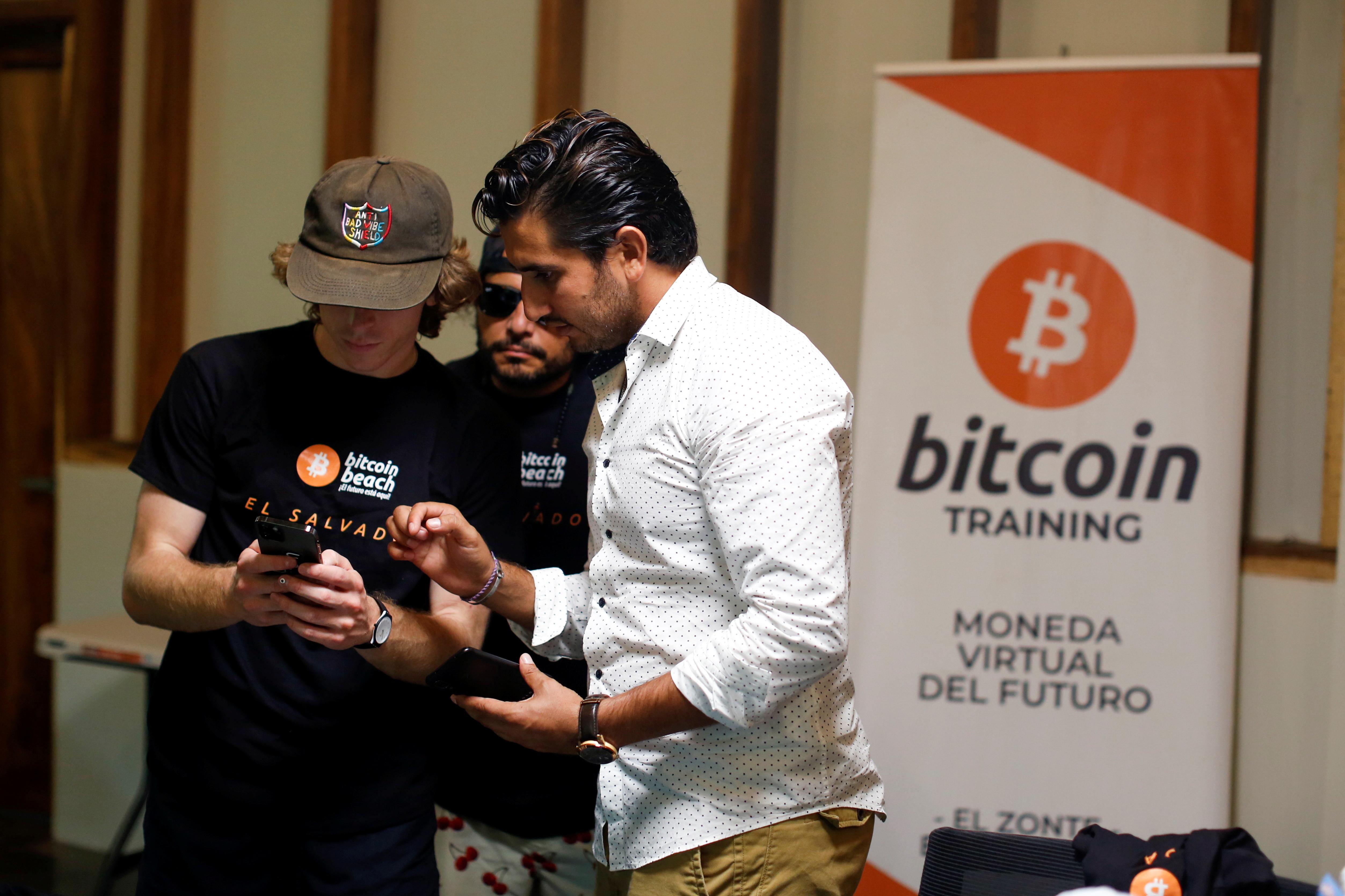 U.S. Bitcoin enthusiast talks with Bitcoin Beach co-founder Roman Martinez at their headquarters at El Zonte Beach in Chiltiupan, El Salvador June 10, 2021. REUTERS/Jose Cabezas