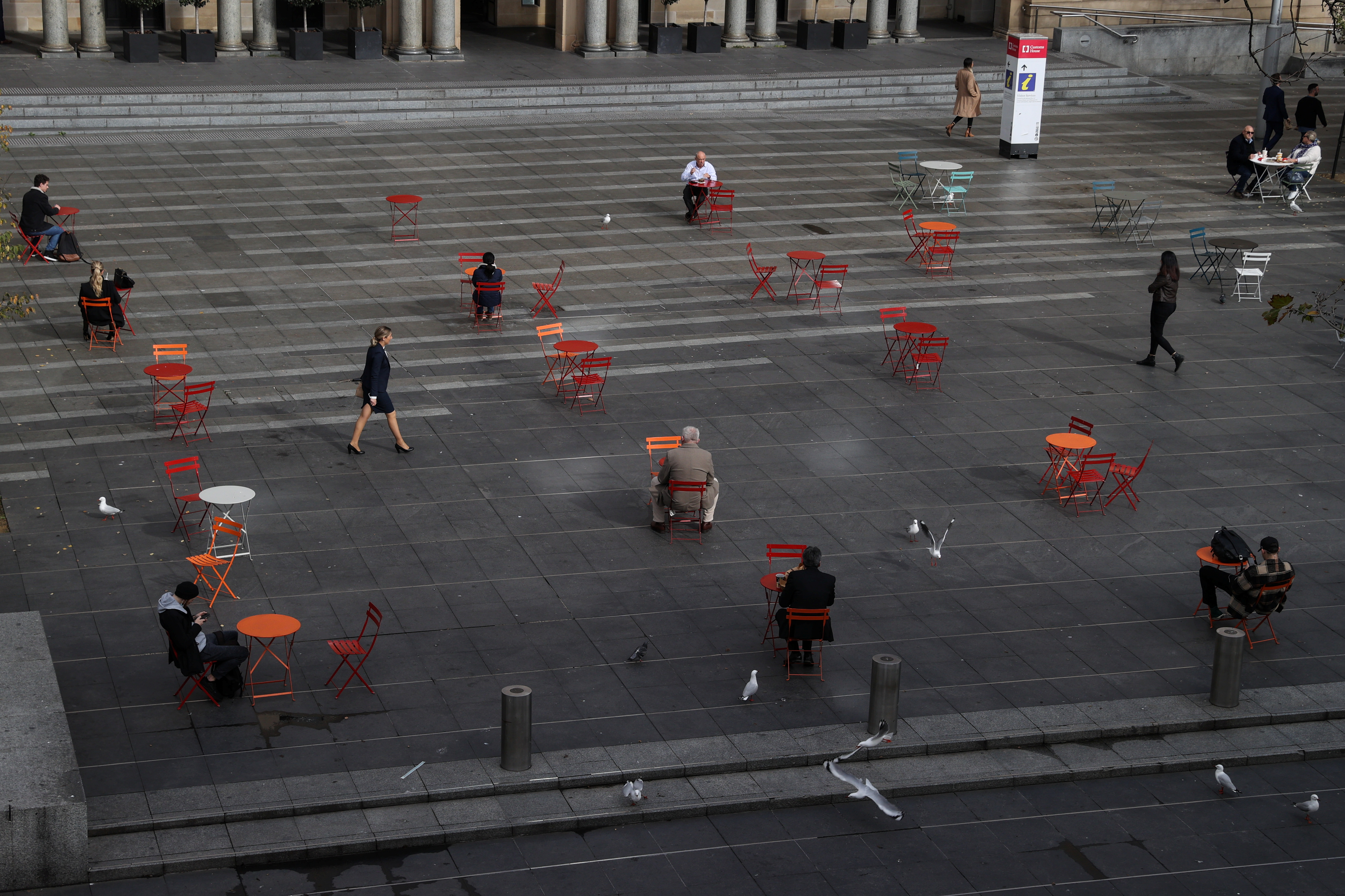 People at Circular Quay sit at socially distanced tables as the state of New South Wales experiences an outbreak of the coronavirus disease (COVID-19) in Sydney, Australia, June 22, 2021.  REUTERS/Loren Elliott