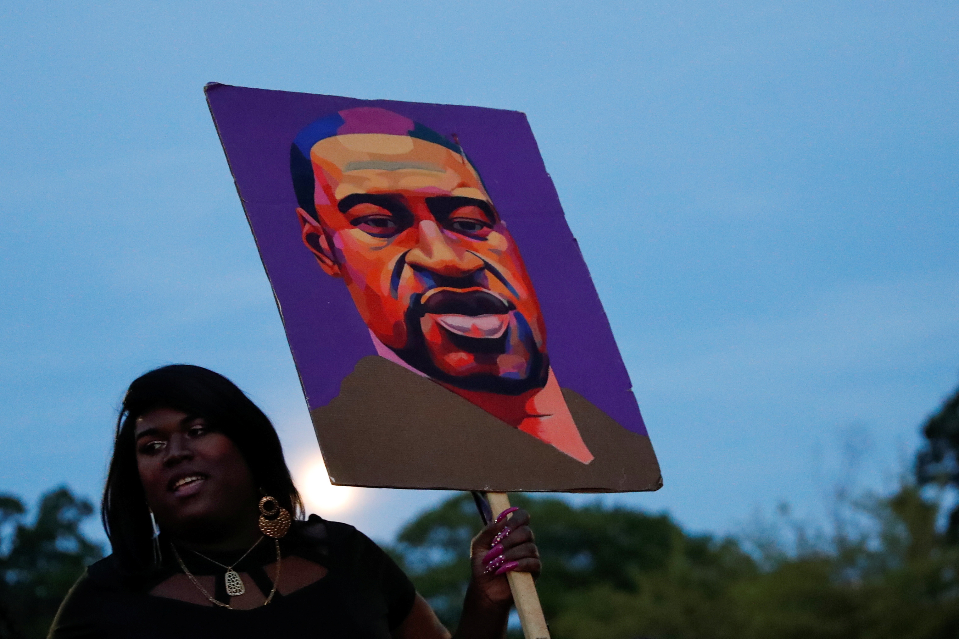 A woman holds a placard depicting George Floyd during a demonstration on the first anniversary of his death, in Brooklyn, New York City, New York, U.S., May 25, 2021. REUTERS/Shannon Stapleton