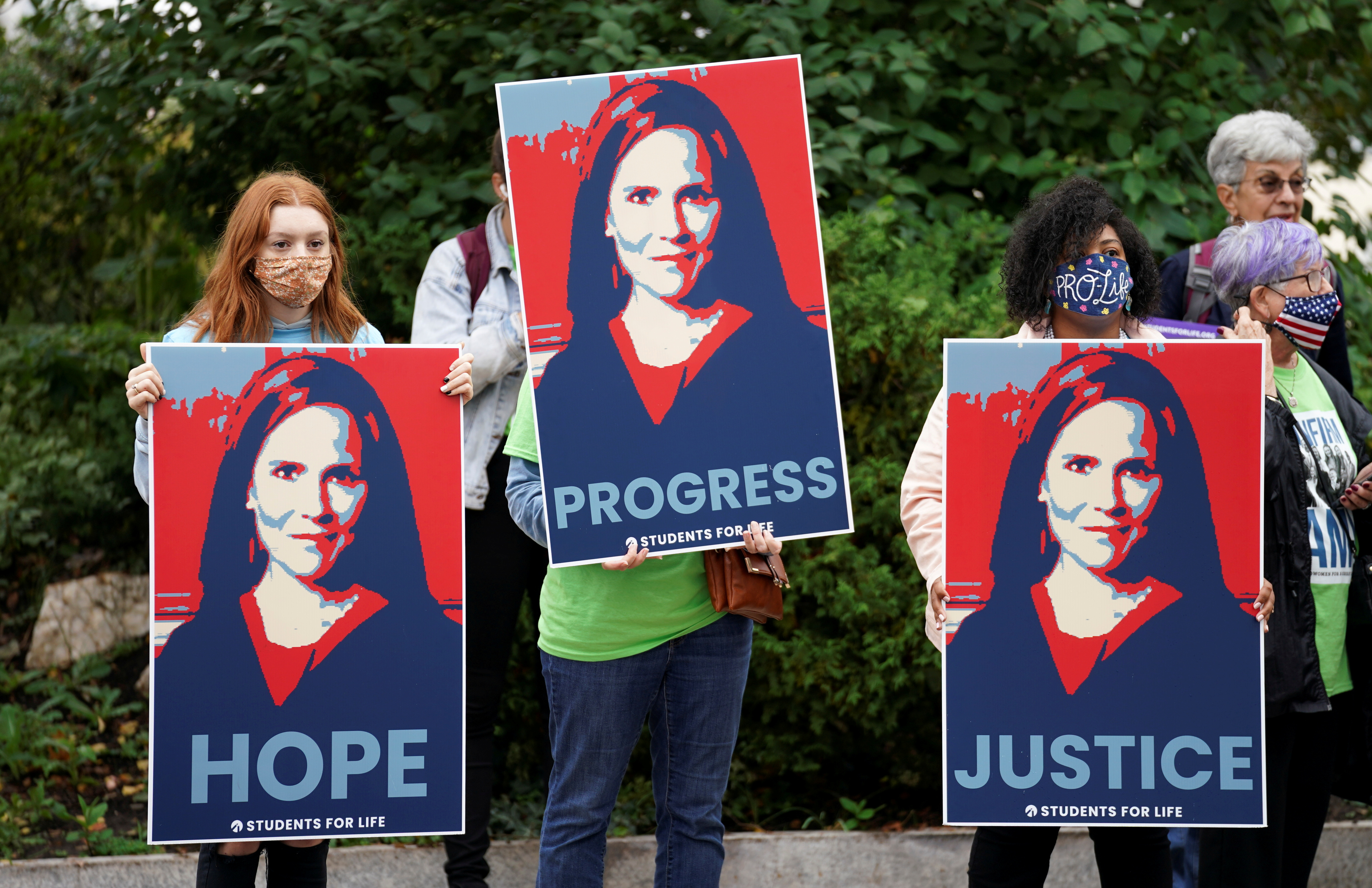 Demonstrators hold signs at the U.S. Capitol supporting the Senate Judiciary Committee hearing of U.S. Supreme Court nominee Judge Amy Coney Barrett in Washington.  REUTERS/Kevin Lamarque
