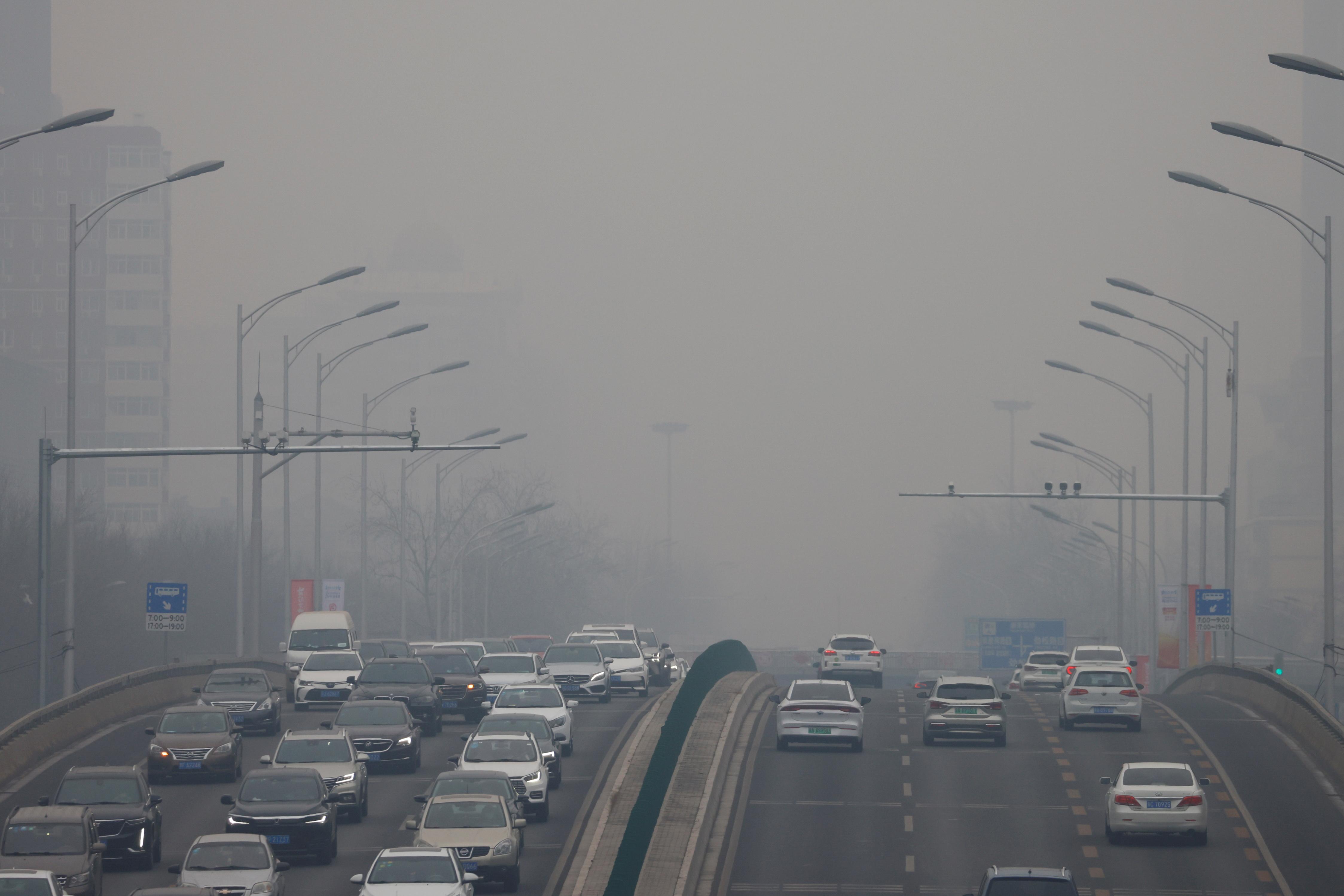 汽车在一天的道路上搬到污染的空气中,冠心病(Covid-19)爆发,在北京,中国2月13日,2021年。路透社/卡洛斯加洛斯罗林斯