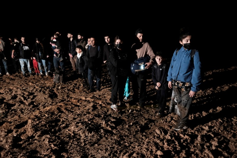 Migrants cross a field next to the Belarus-Latvia border near Vorzova, Latvia August 11, 2021. REUTERS/Ints Kalnins