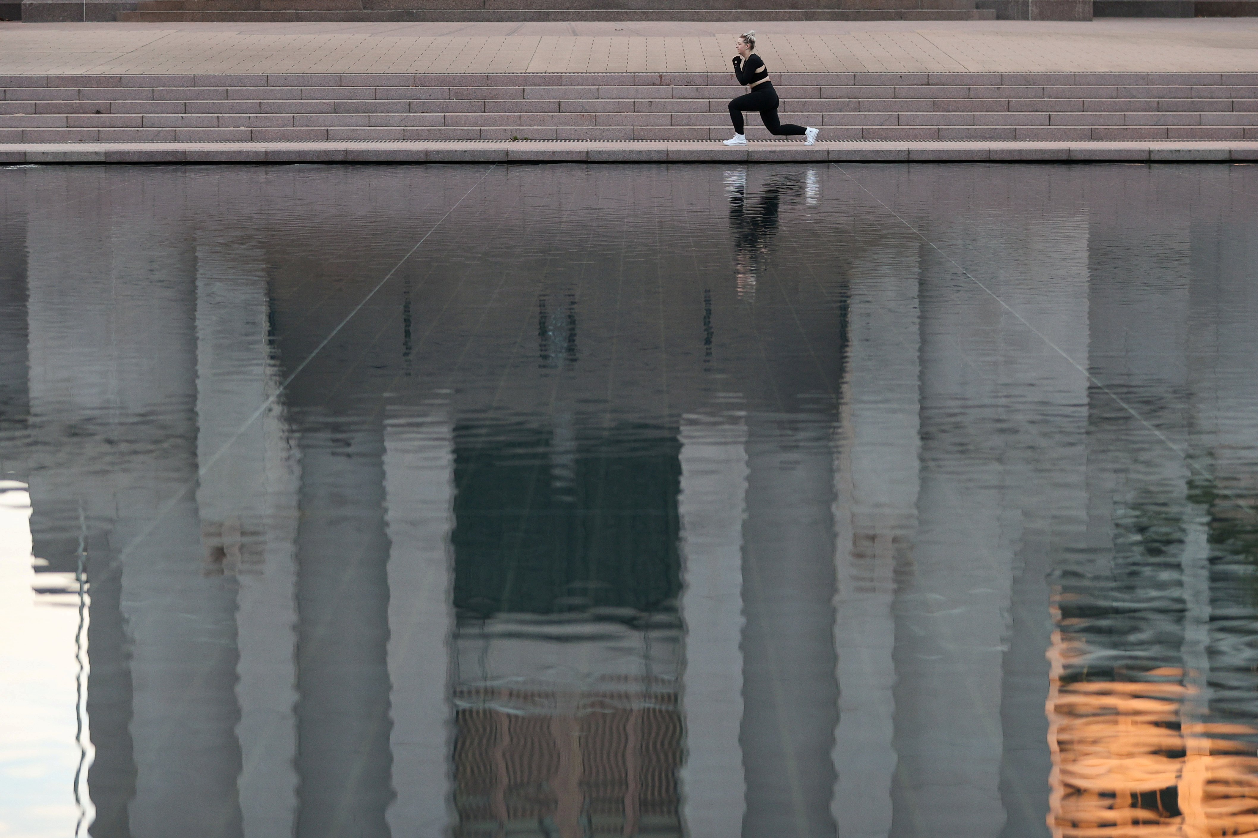 A woman exercises on the empty steps in front of the Anzac Memorial at the Pool of Reflection as gyms are closed during a lockdown to curb the spread of a coronavirus disease (COVID-19) outbreak in Sydney, Australia, July 22, 2021.  REUTERS/Loren Elliott/File Photo