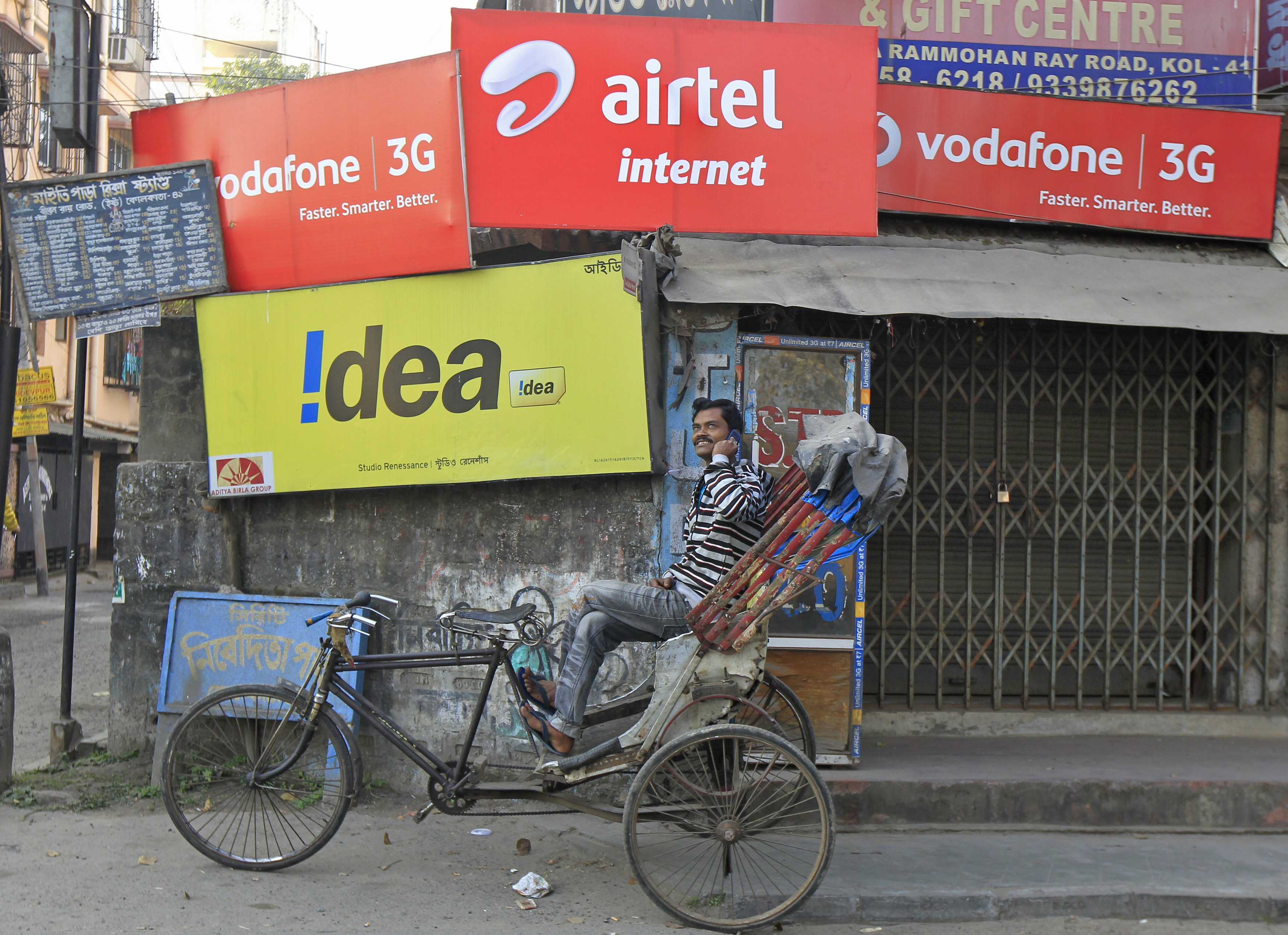 A rickshaw puller speaks on his mobile phone as he waits for customers in front of advertisement billboards belonging to telecom companies in Kolkata February 3, 2014. REUTERS/Rupak De Chowdhuri/Files