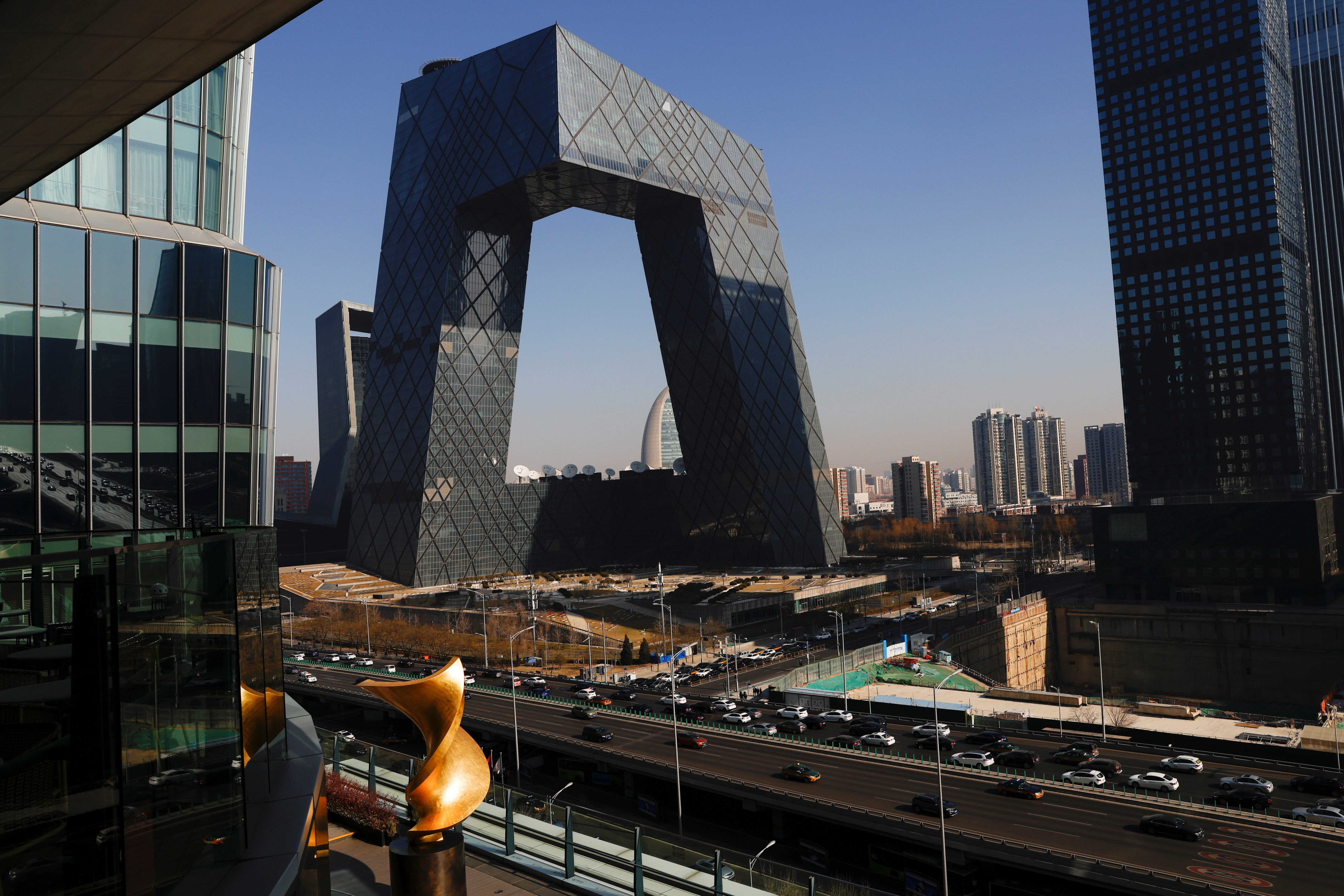 Cars travel past the CCTV headquarters, the home of Chinese state media outlet CCTV and its English-language sister channel CGTN, in Beijing, China February 5, 2021. REUTERS/Carlos Garcia Rawlins/File Photo