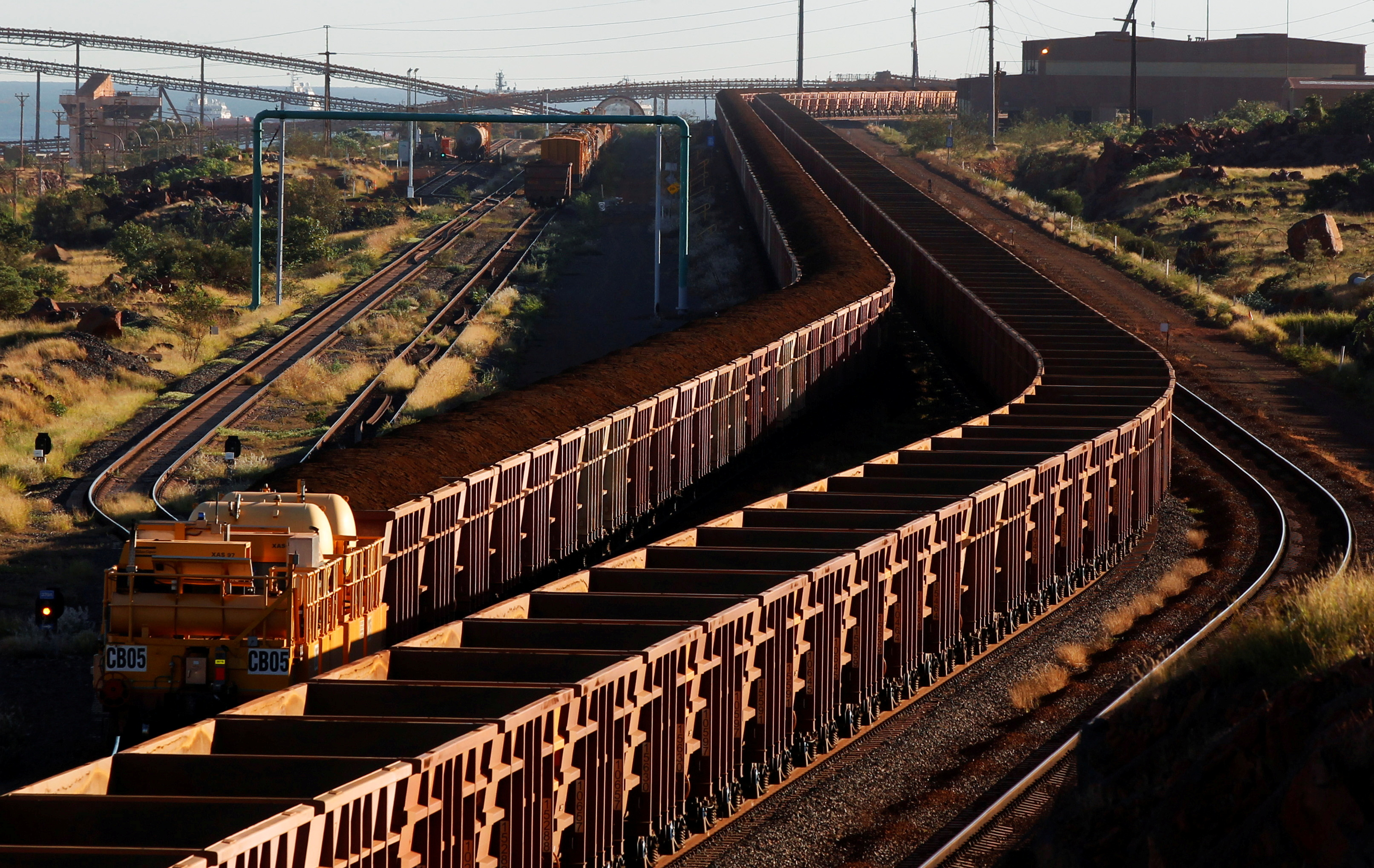 A train loaded with iron ore travels towards the Rio Tinto Parker Point iron ore facility as an empty train leaves in Dampier at the Pilbarra region in western Australia April 20, 2011.  REUTERS/Daniel Munoz//File Photo