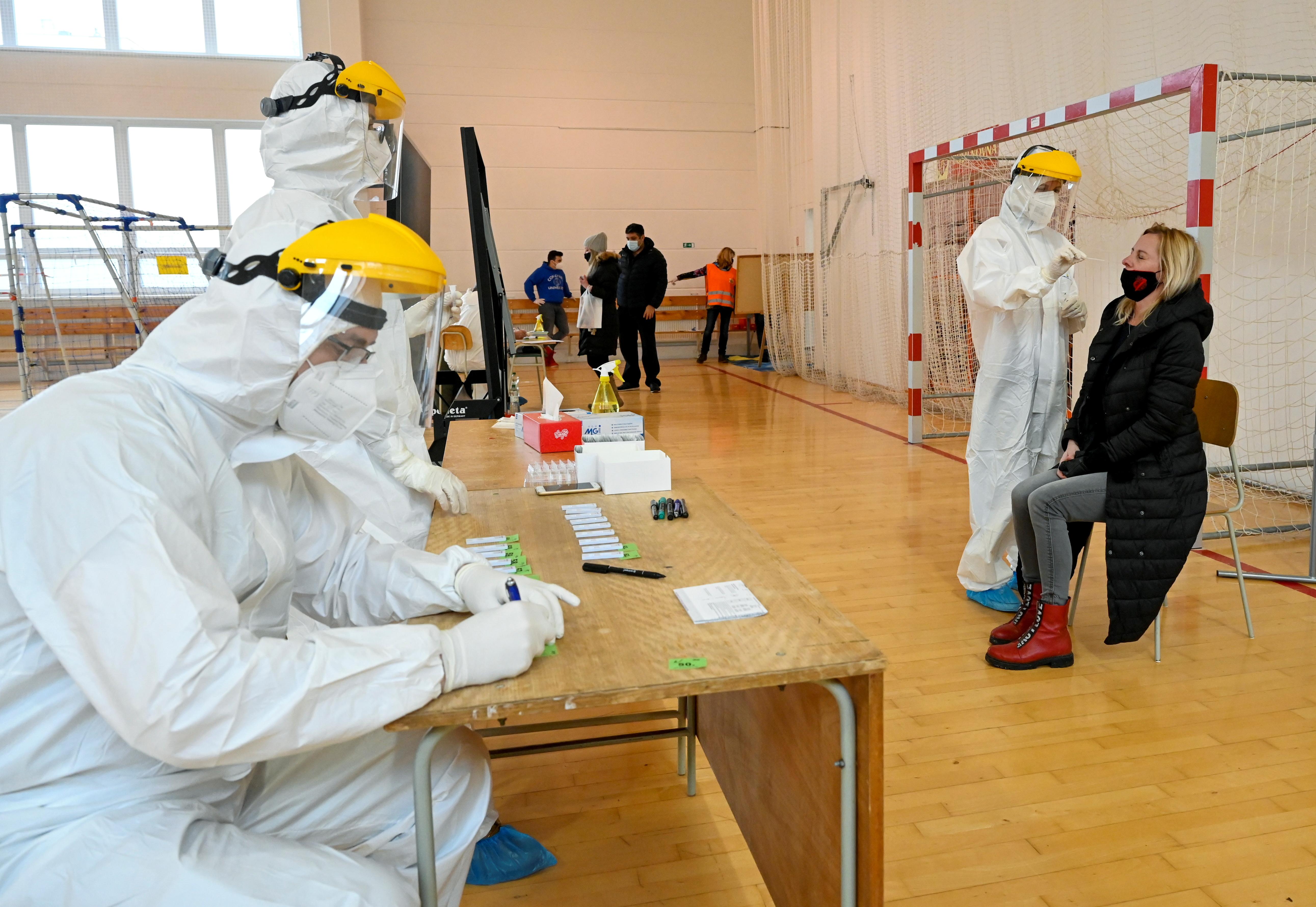 Polish healthcare workers (L) help during a mass nationwide testing for coronavirus disease (COVID-19) in Zilina, Slovakia, January 23, 2021. REUTERS/Radovan Stoklasa/File Photo