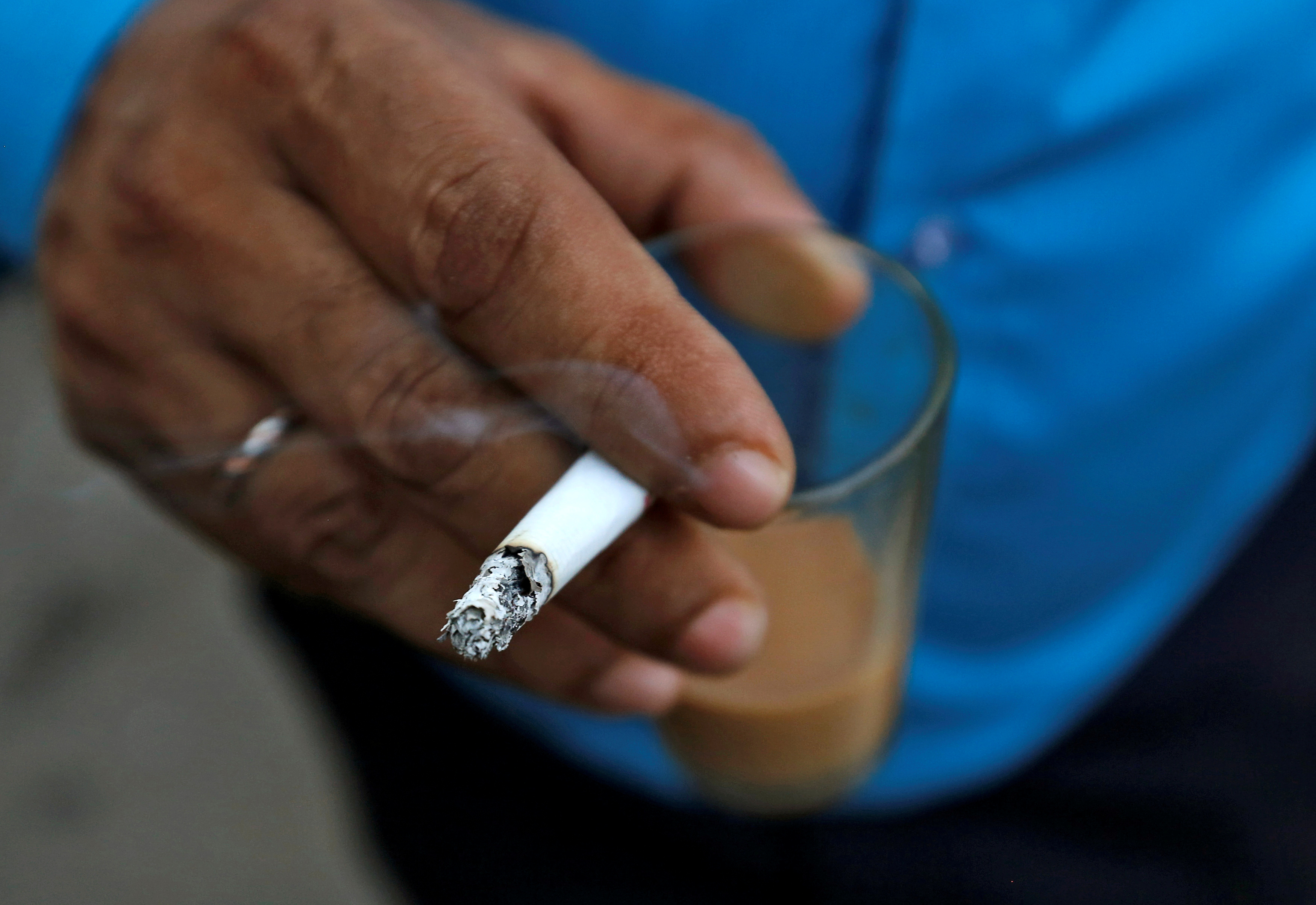 A man smokes a cigarette along a road in Mumbai, India, October 26, 2016. REUTERS/Danish Siddiqui