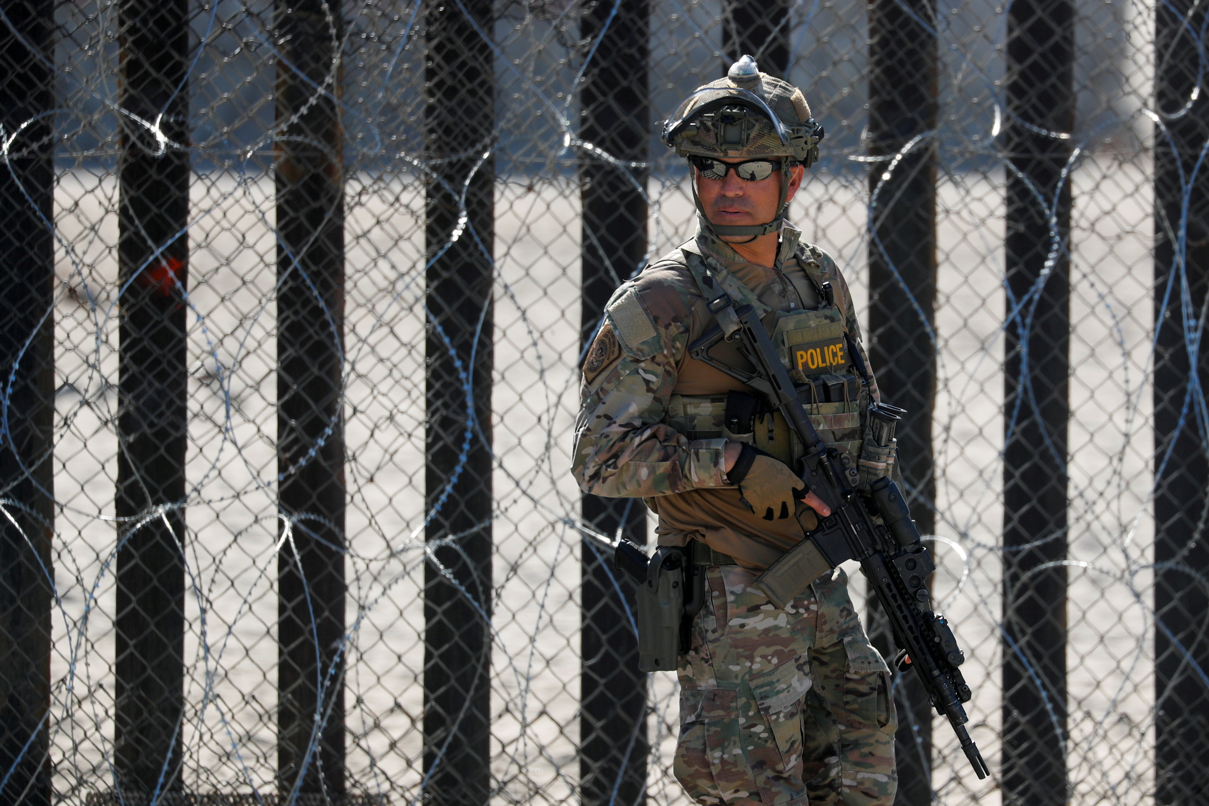 An armed U.S. Customs and Border Patrol agent stands watch at the border fence next to the beach in Tijuana, at the Border State Park in San Diego, California, U.S. November 16, 2018.   REUTERS/Mike Blake/File Photo