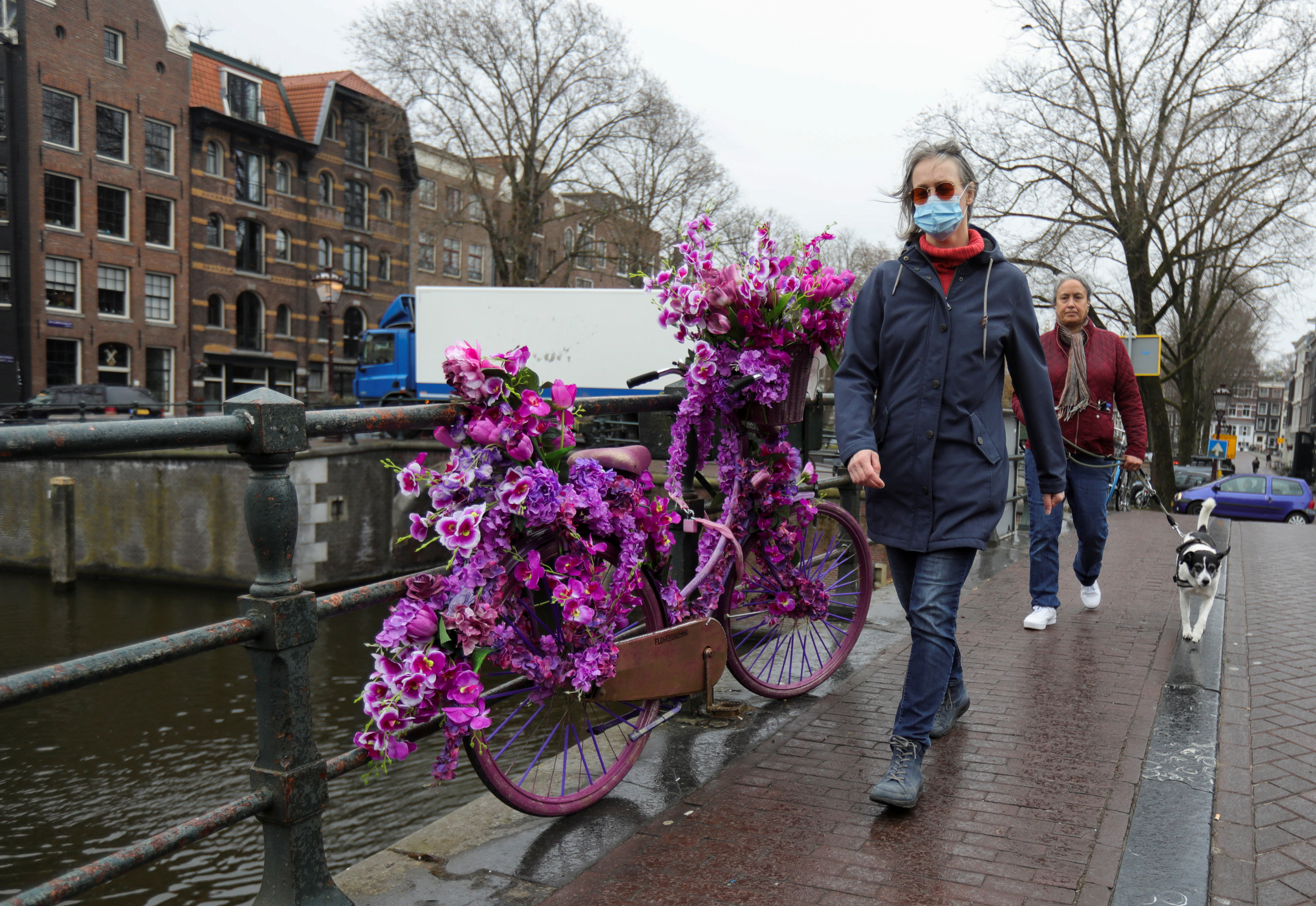 People walk past a bike with flowers at the Prinsengracht in Amsterdam, Netherlands March 10, 2021. Picture taken March 10, 2021. REUTERS/Eva Plevier