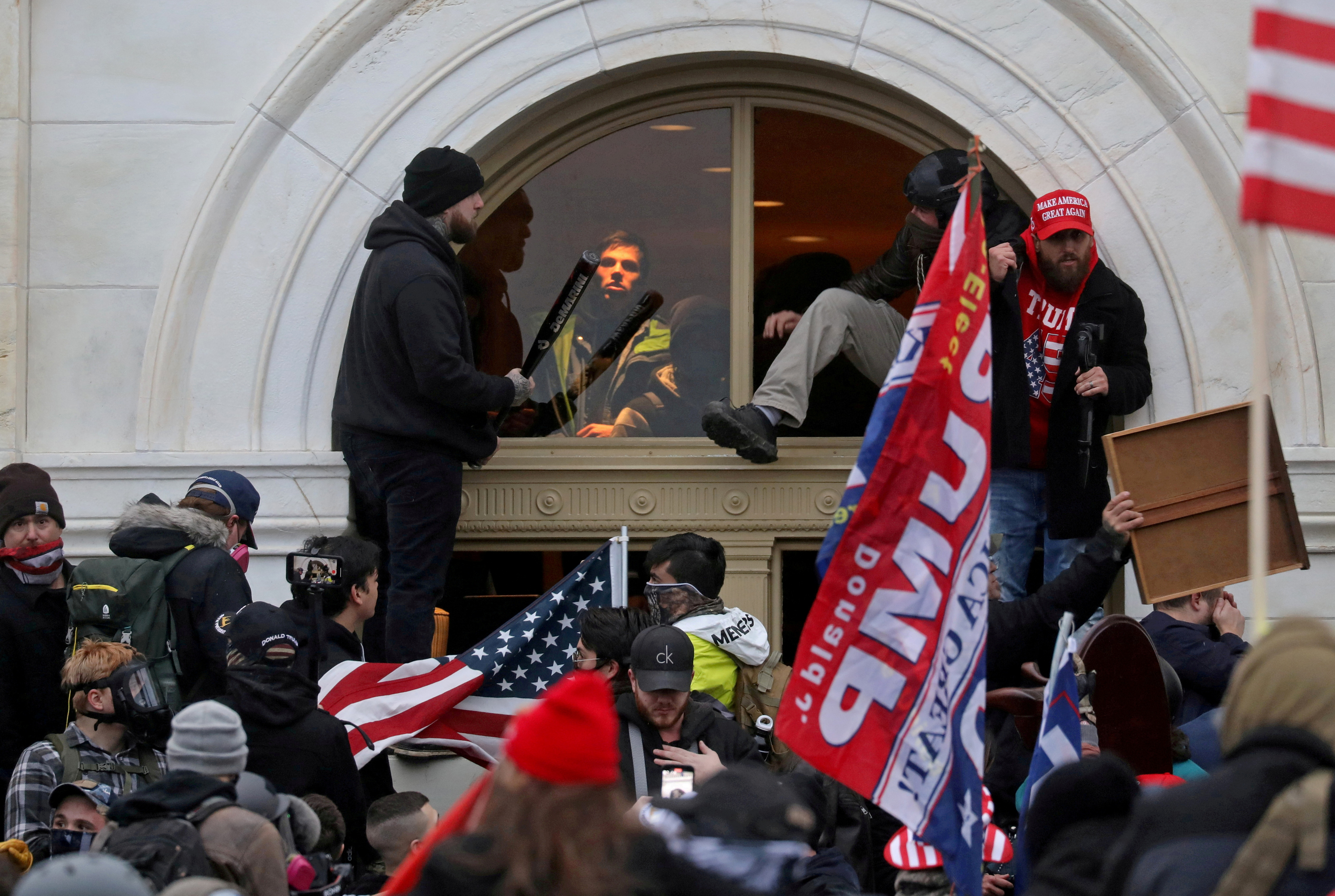 A mob of supporters of then-U.S. President Donald Trump climb through a window they broke as they storm the U.S. Capitol Building in Washington, U.S., January 6, 2021. REUTERS/Leah Millis/File Photo