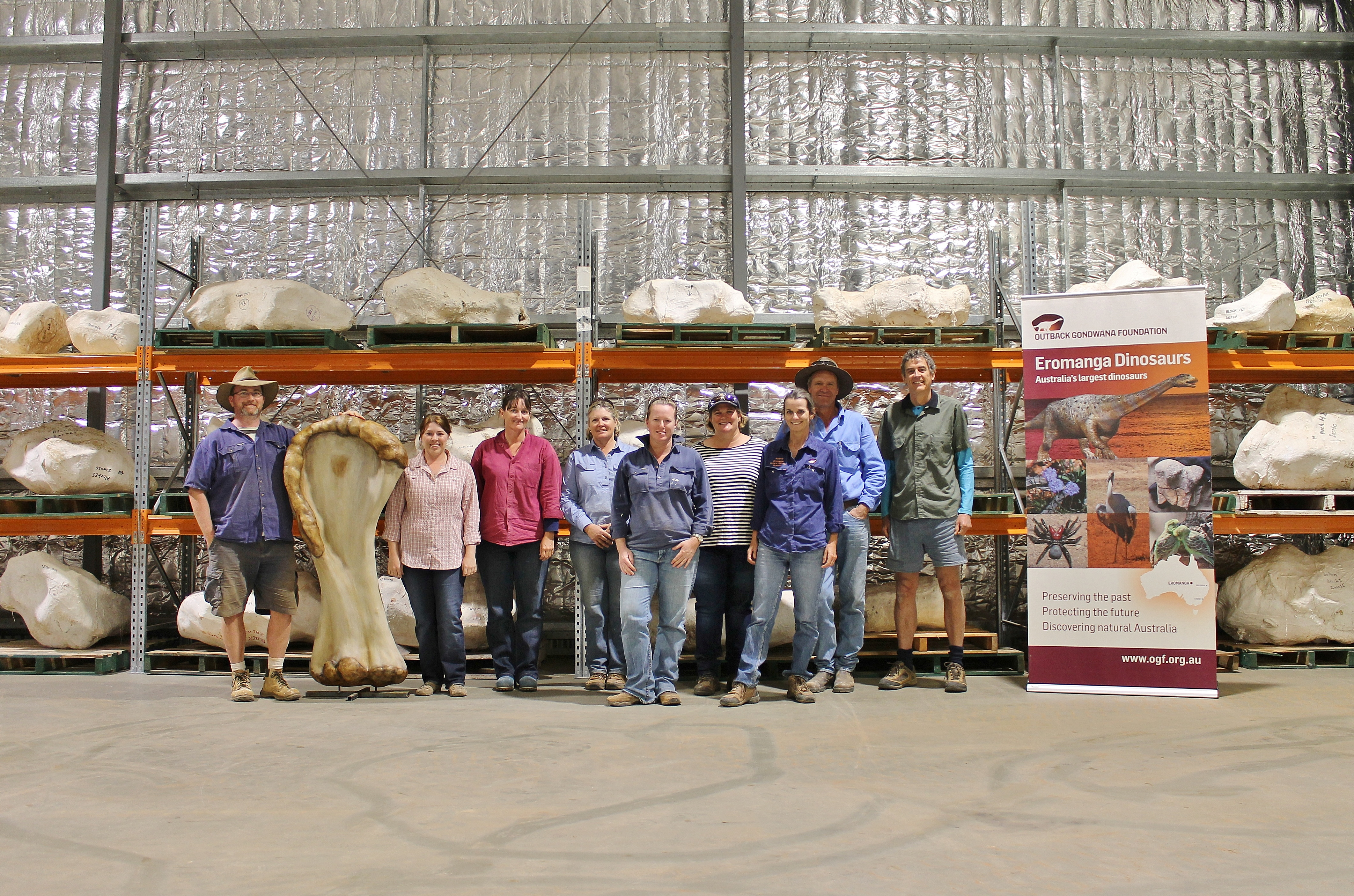 """A field research team poses with a 3D reconstruction of the humerus bone and other dinosaur bones in plaster jackets from """"Cooper,"""" a new species of dinosaur discovered in Queensland and recognised as the largest ever found in Australia, in this undated handout image made available to Reuters on June 8, 2021 in Eromanga, Australia. Eromanga Natural History Museum/Handout via REUTERS"""