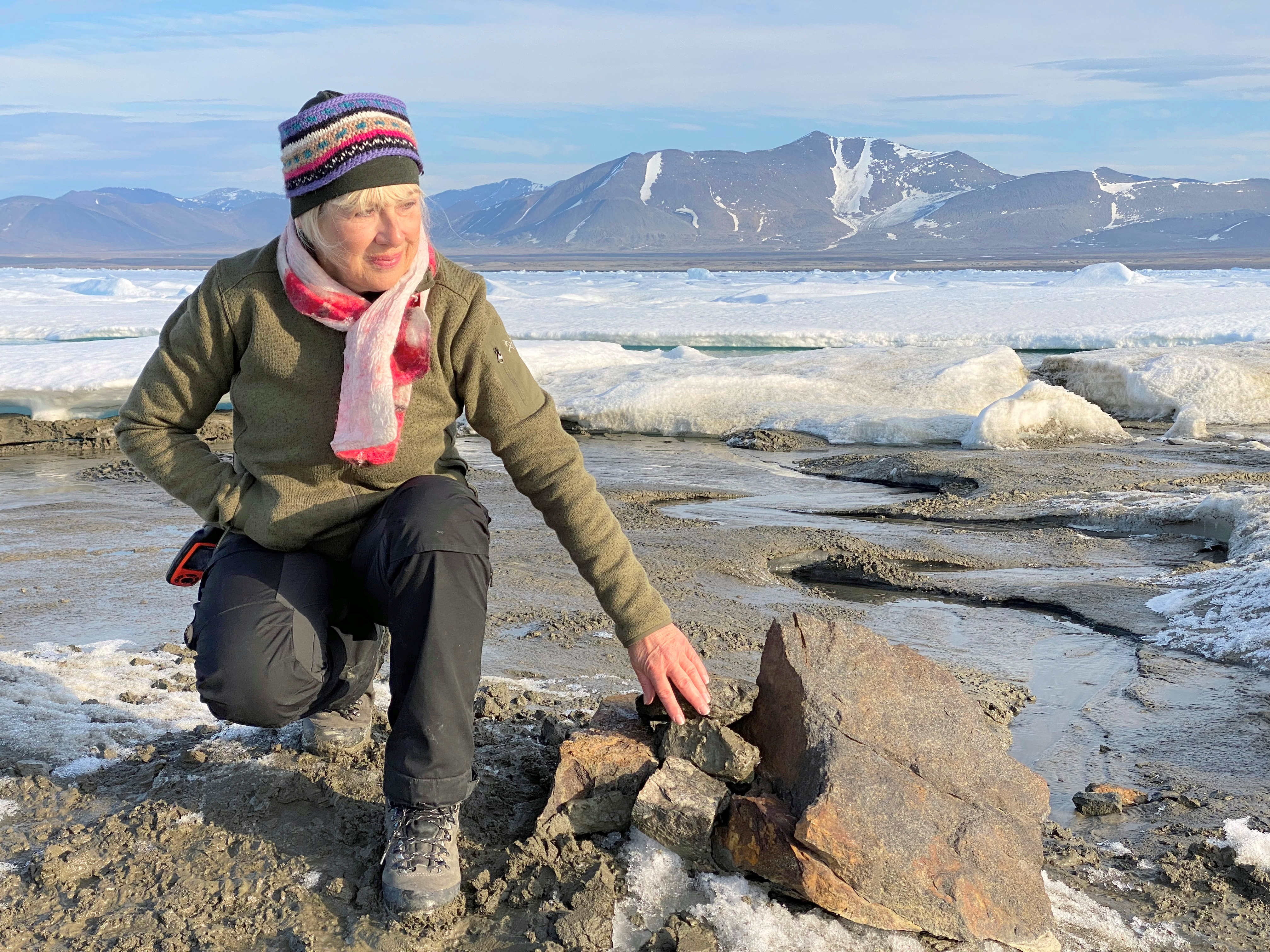 An undated handout image of Swiss entrepreneur Christiane Leister, creator of the Leister Foundation that financed an expedition which discovered a tiny island off the coast of Greenland which they say is the world's northernmost point of land, in front of a cairn in which expedition members left a message with details of their visit. Julian Charriere/via REUTERS