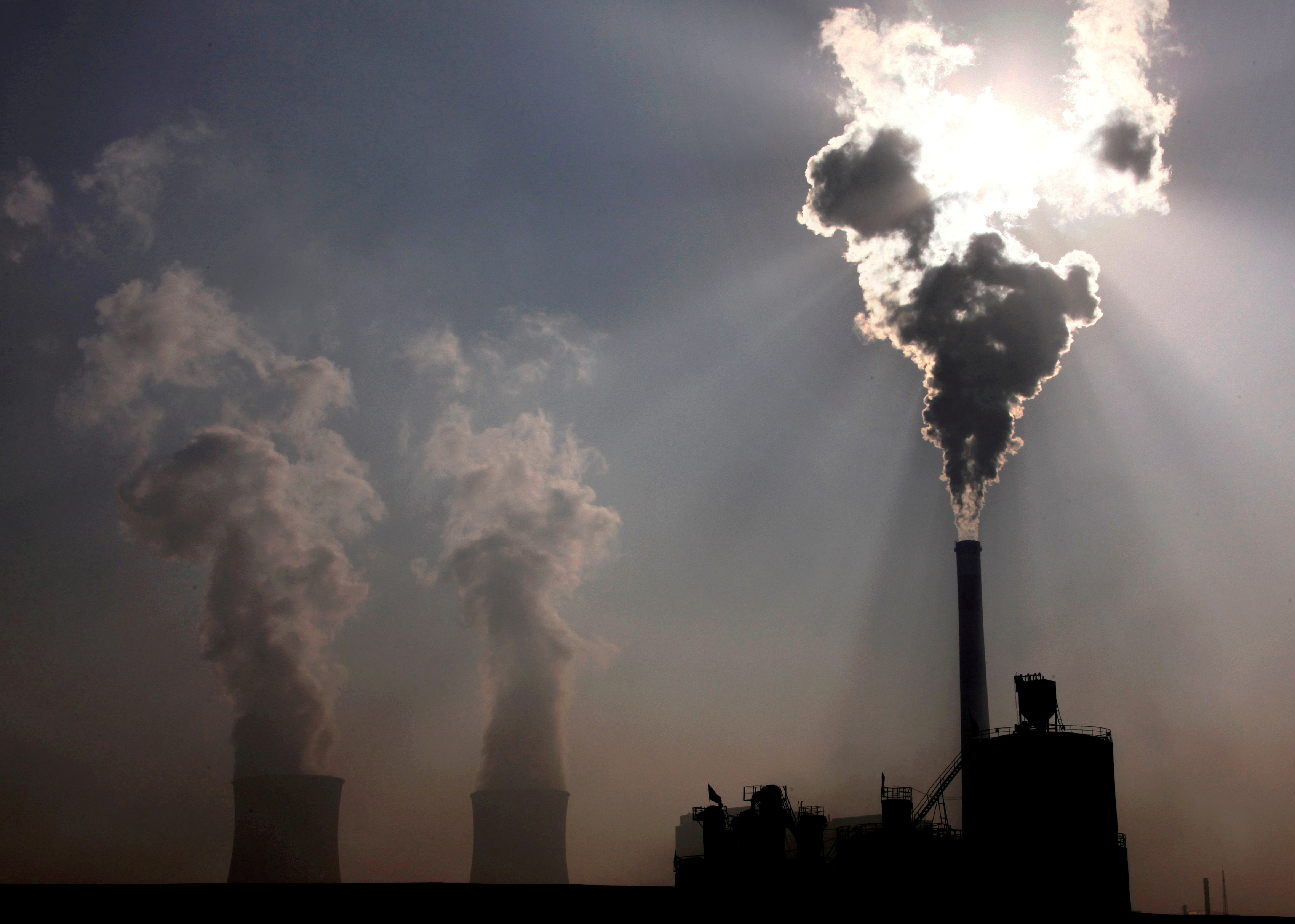 A coal-burning power plant can be seen behind a factory in the city of Baotou, in China's Inner Mongolia Autonomous Region, October 31, 2010.  REUTERS/David Gray/File Photo
