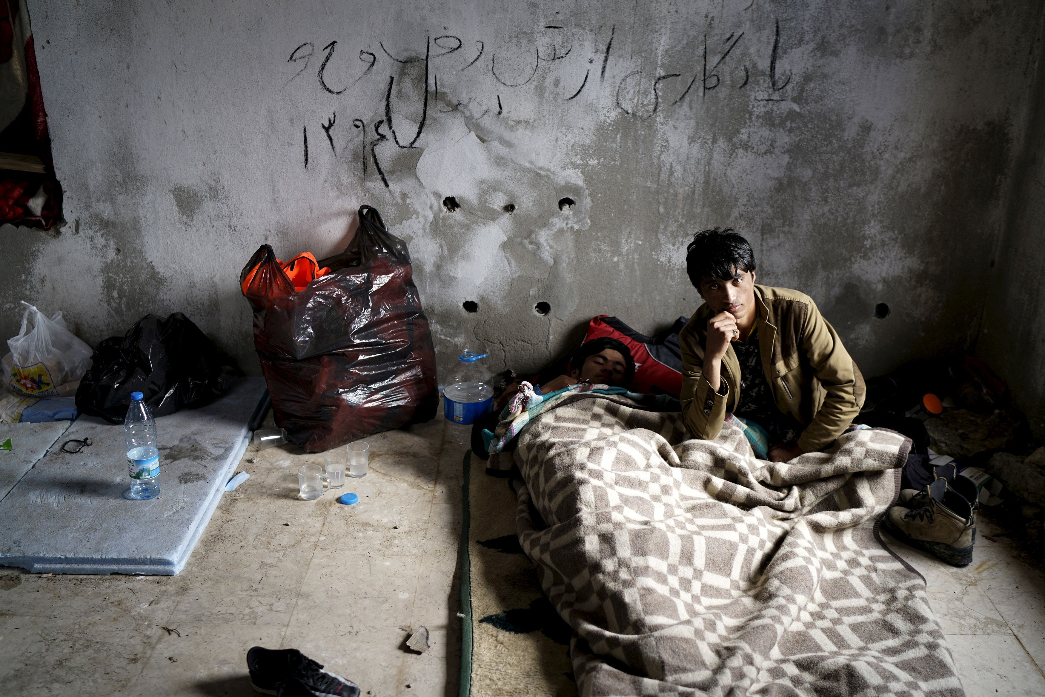Afghan refugees rest in an old abandoned beach house as they wait to board a dinghy sailing off for the Greek island of Chios, while they try to travel from the western Turkish coastal town of Cesme, in Izmir province, Turkey, March 6, 2016. REUTERS/Umit Bektas/File Photo