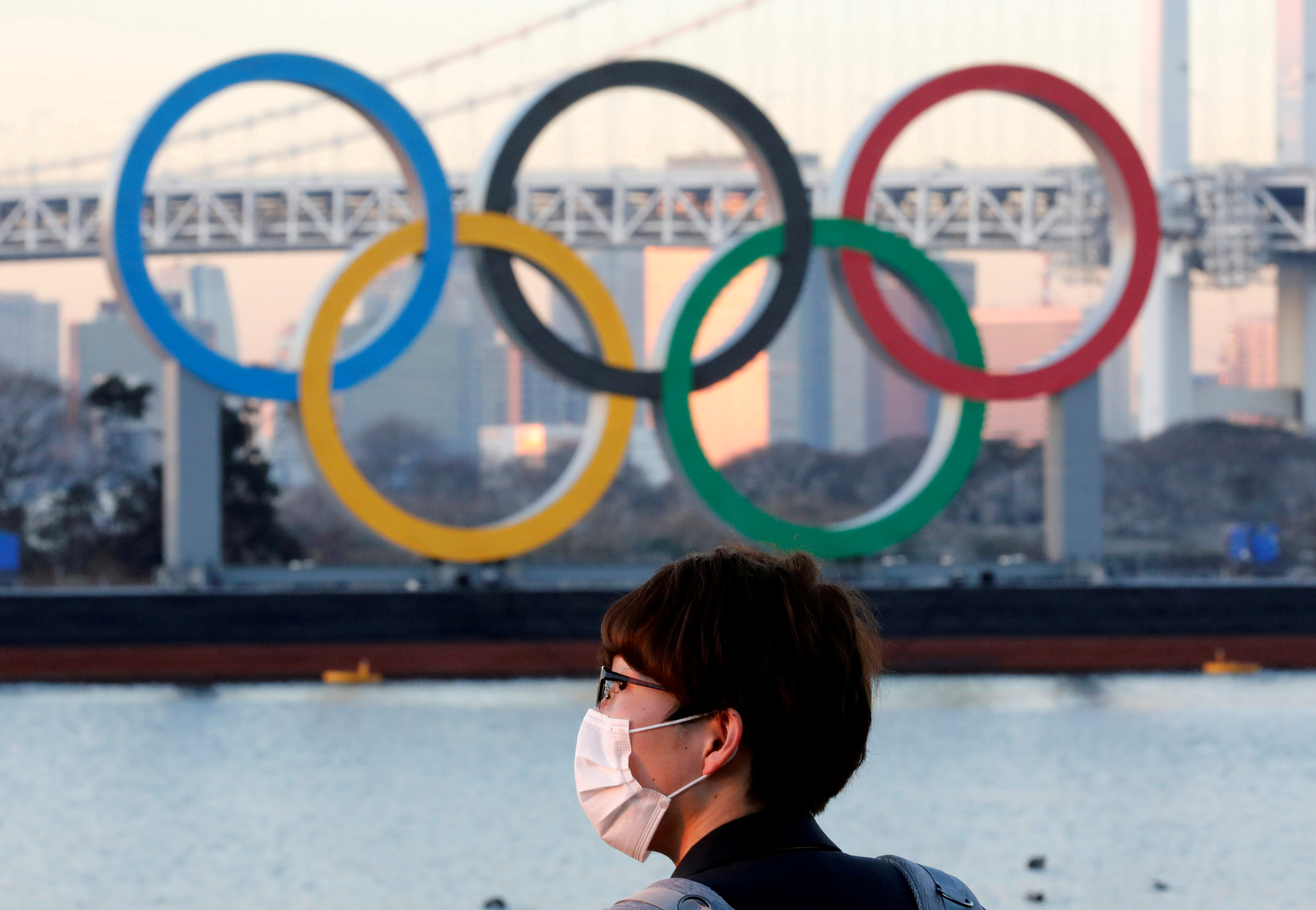A man wears a protective mask amid the coronavirus (COVID-19) outbreak in front of the giant Olympic rings in Tokyo, Japan, January 13, 2021. REUTERS/Kim Kyung-Hoon/File Photo