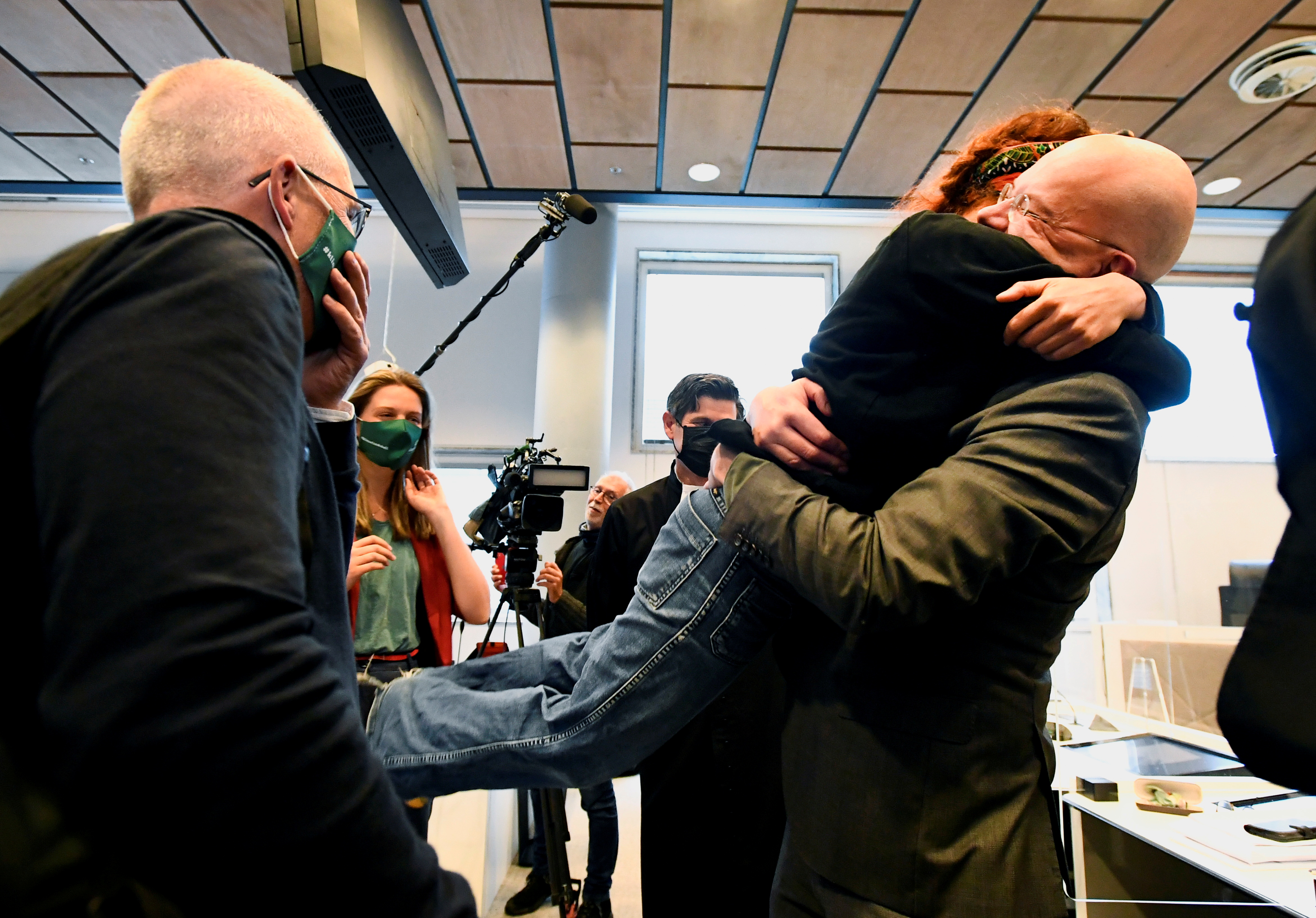 Donald Pols, Director of Milieudefensie (Friends of the Earth),  hugs Hilde Brontsema, as they react after a verdict in a case brought on against Shell by environmentalist and human rights groups, including Greenpeace and Friends of the Earth, who demand the energy firm to cut its reliance on fossil fuels, in The Hague, Netherlands, May 26, 2021. REUTERS/Piroschka van de Wouw