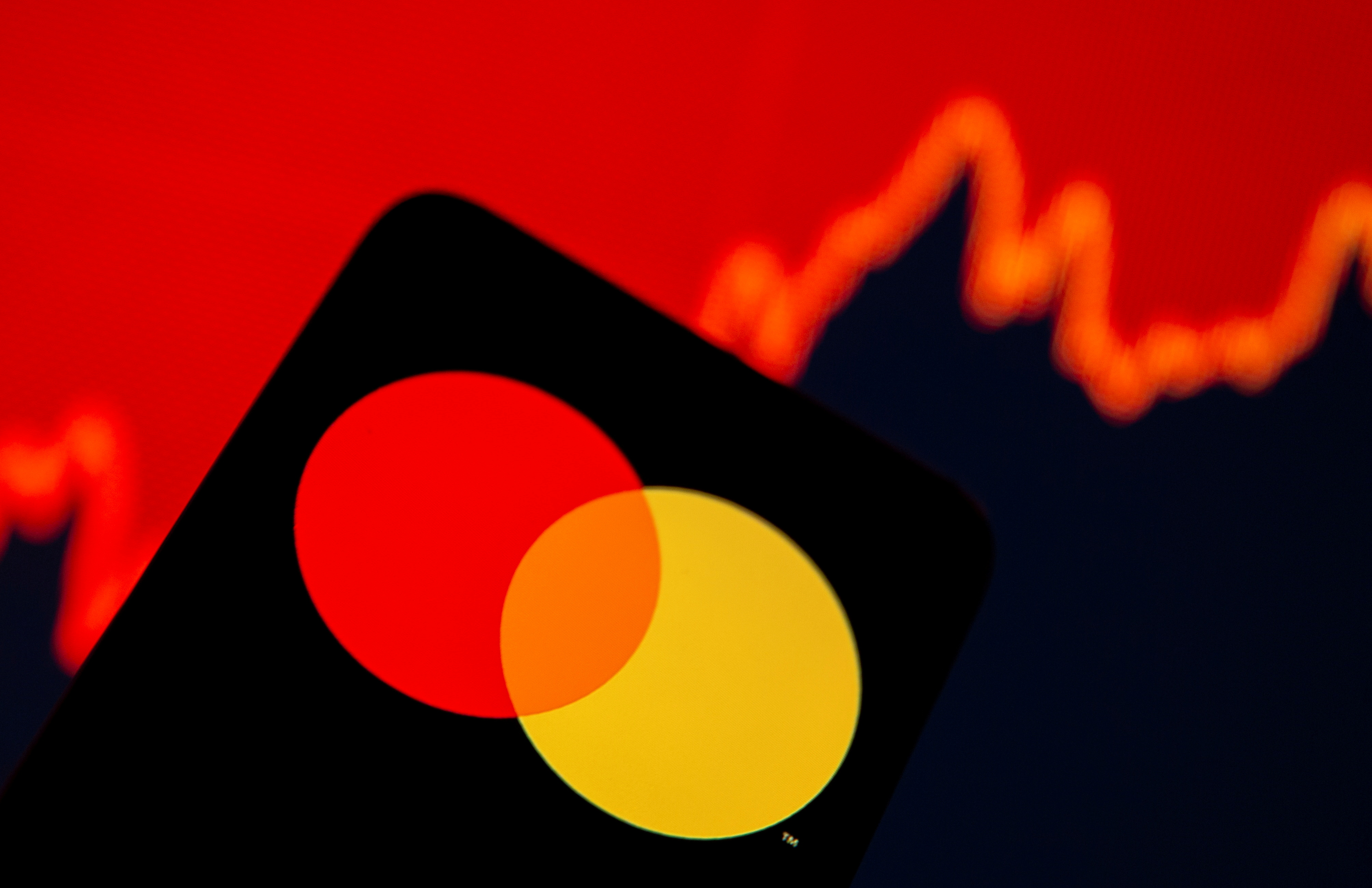 Smartphone with Mastercard logo is seen in front of displayed stock graph in this illustration taken, July 15, 2021. REUTERS/Dado Ruvic/Illustration