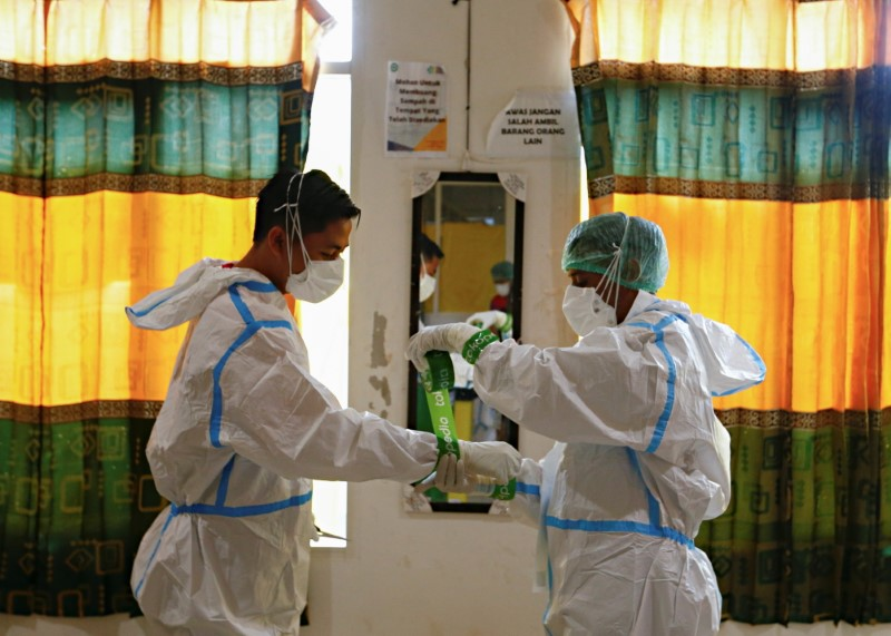 Healthcare workers wearing PPE (personal protective equipment) prepare themselves to treat patients at the emergency hospital for the coronavirus disease (COVID-19) in Jakarta, Indonesia, June 17, 2021. REUTERS/Ajeng Dinar Ulfiana