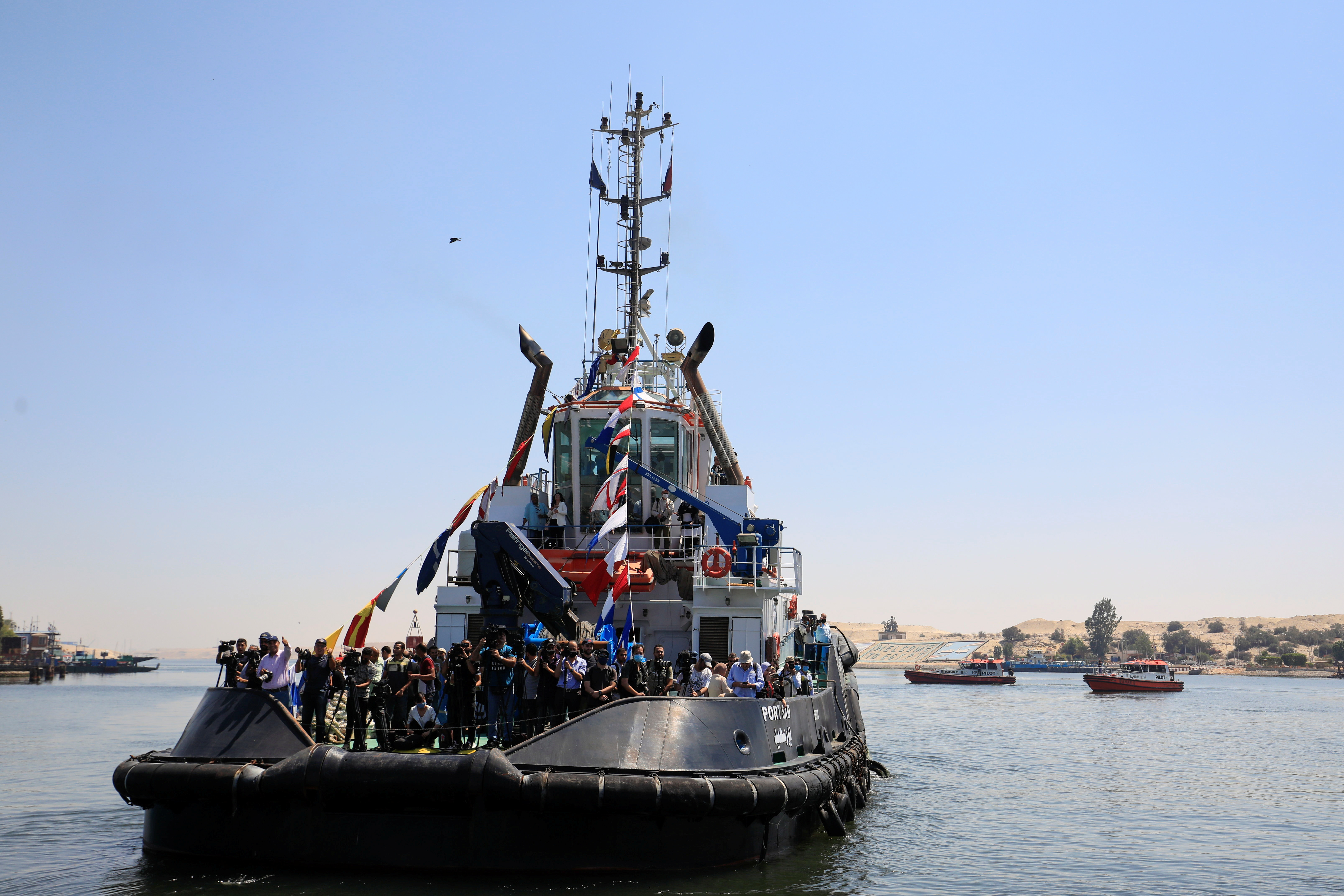 Members of the media ride on a boat on their way to the area where the Ever Given, one of the world's largest container ships, sets sail to leave the Suez Canal after the canal authority reached a settlement with the vessel's owner and insurers, in Ismailia, Egypt, July 7, 2021. REUTERS/Amr Abdallah Dalsh