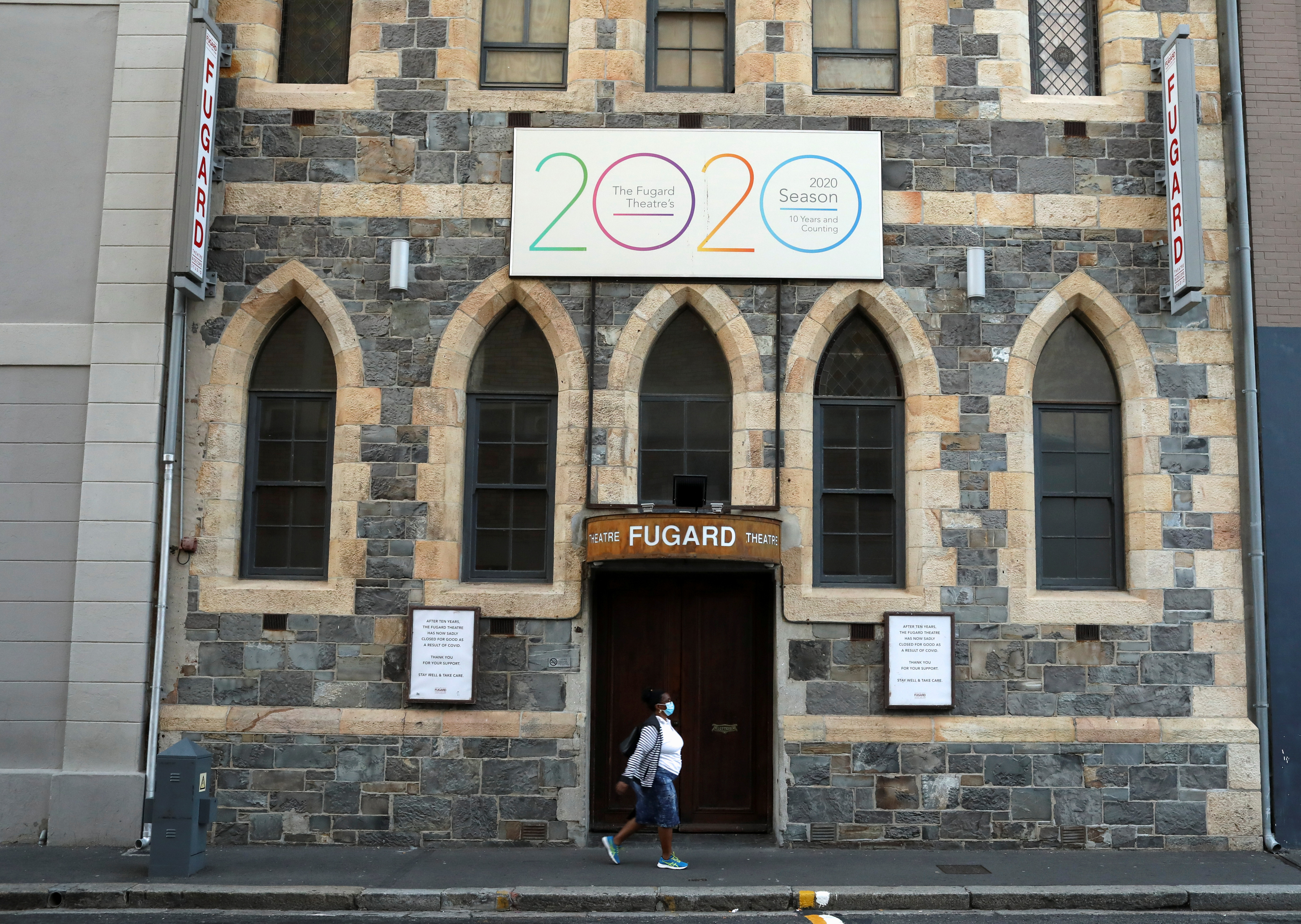A woman walks past signs announcing the permanent closure of the Fugard Theatre as a result of the coronavirus disease (COVID-19) pandemic in Cape Town, South Africa, April 6, 2021. REUTERS/Mike Hutchings